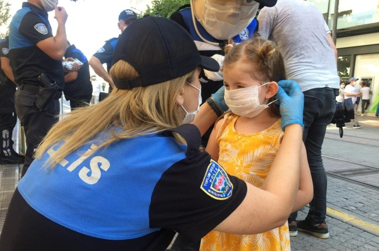 Policewoman helps child to wear a mask correctly as police mascot raises awareness about the usage of masks in public spaces in Eskişehir, Turkey, July 22, 2020. (IHA Photo)