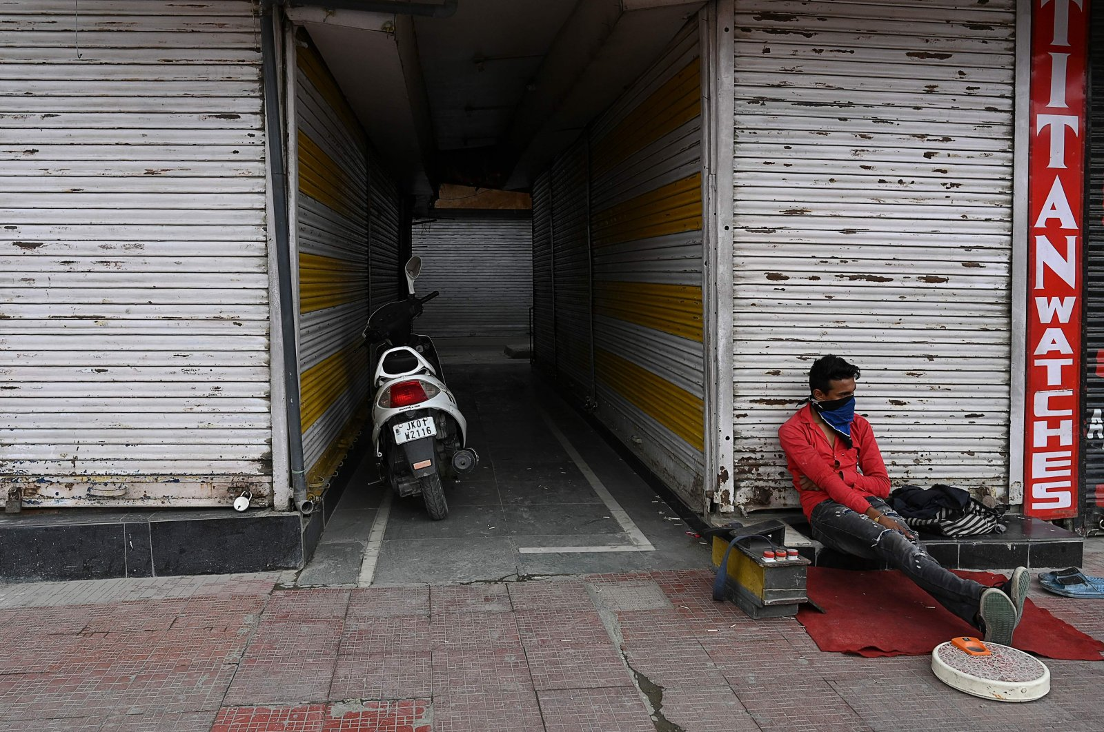 A cobbler sits in front of closed shops as he waits for customers during a lockdown, Srinagar, July 21, 2020. (AFP Photo)