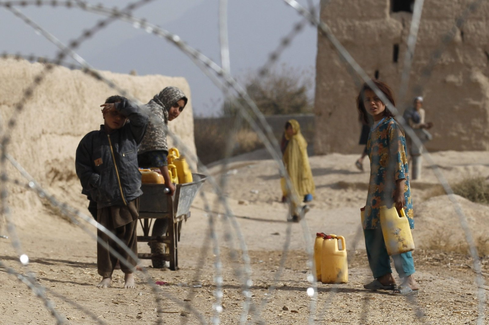 Afghan children look from behind razor wire at an outpost in Zhari district in Kandahar province, Afghanistan, Nov. 20, 2010. (Reuters Photo)