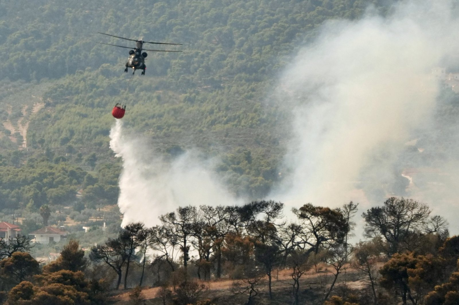 A firefighting helicopter makes a water drop as a wildfire burns near the village of Galataki, Greece, July 23, 2020. (Reuters Photo)