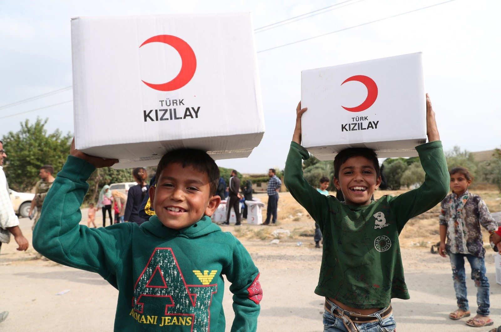 Children carry aid packages delivered by the Turkish Red Crescent in Tal Abyad, Syria, Oct. 27, 2019. (DHA Photo)