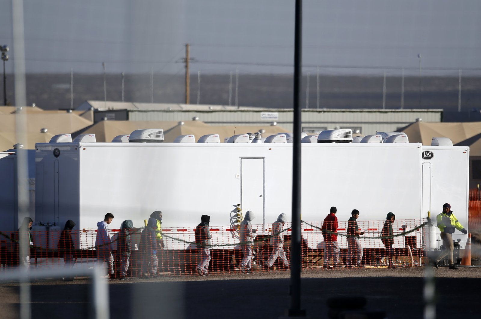 In this Dec. 13, 2018 file photo migrant teens walk in a line through the Tornillo detention camp in Tornillo, Texas. (AP File Photo)