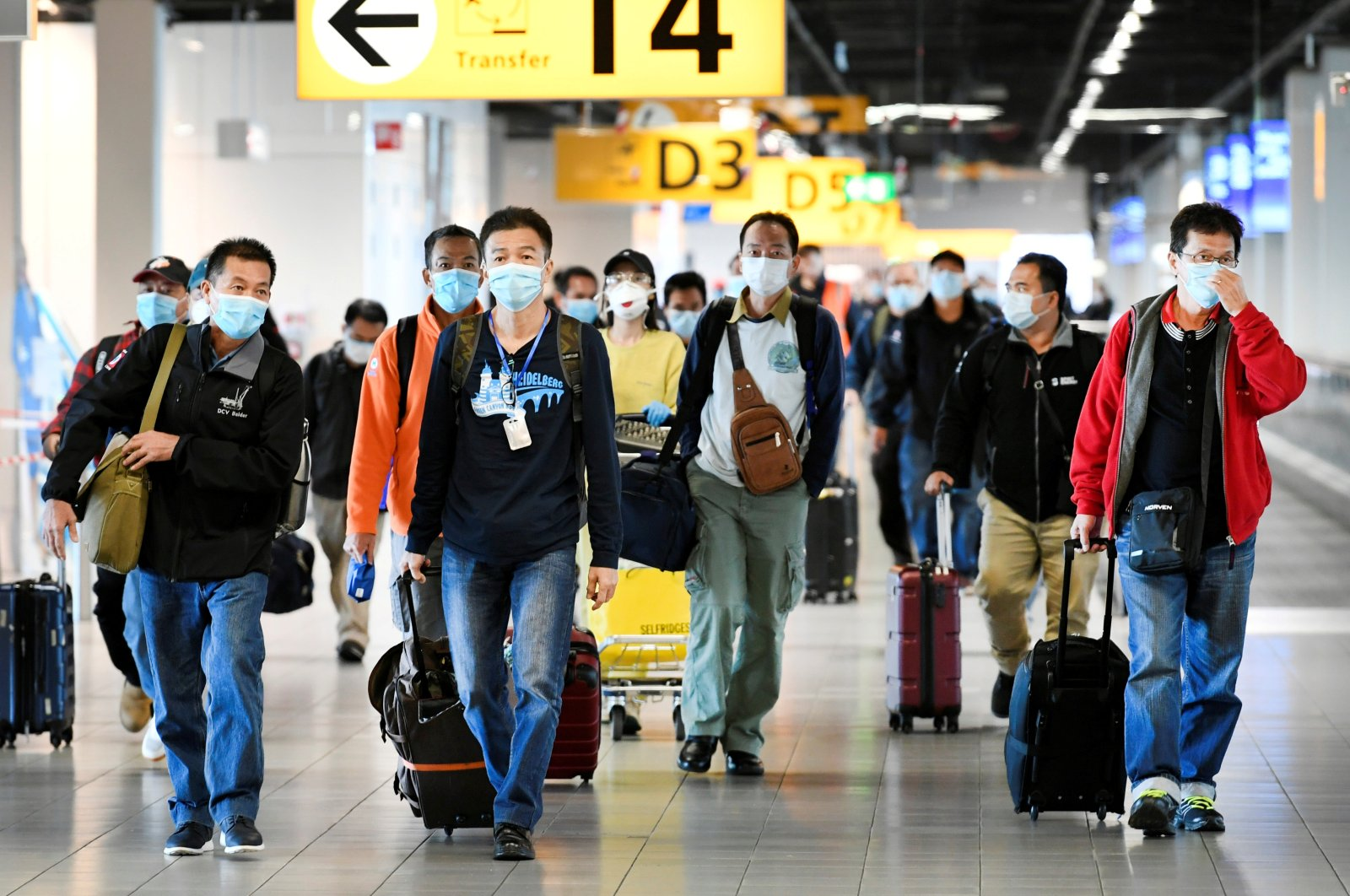 People wearing protective face masks walk, as Schiphol Airport reduces its flights due to the coronavirus disease (COVID-19) outbreak, in Amsterdam, Netherlands on April 2, 2020. (Reuters Photo)