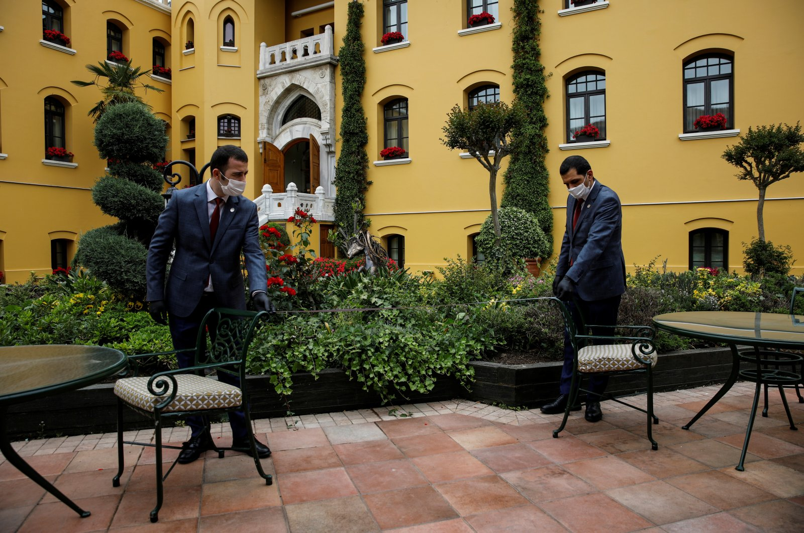 Four Seasons Sultanahmet Hotel staff members measure the distance between tables and chairs as part of COVID-19 measures in Istanbul, May 21, 2020. (Reuters Photo)