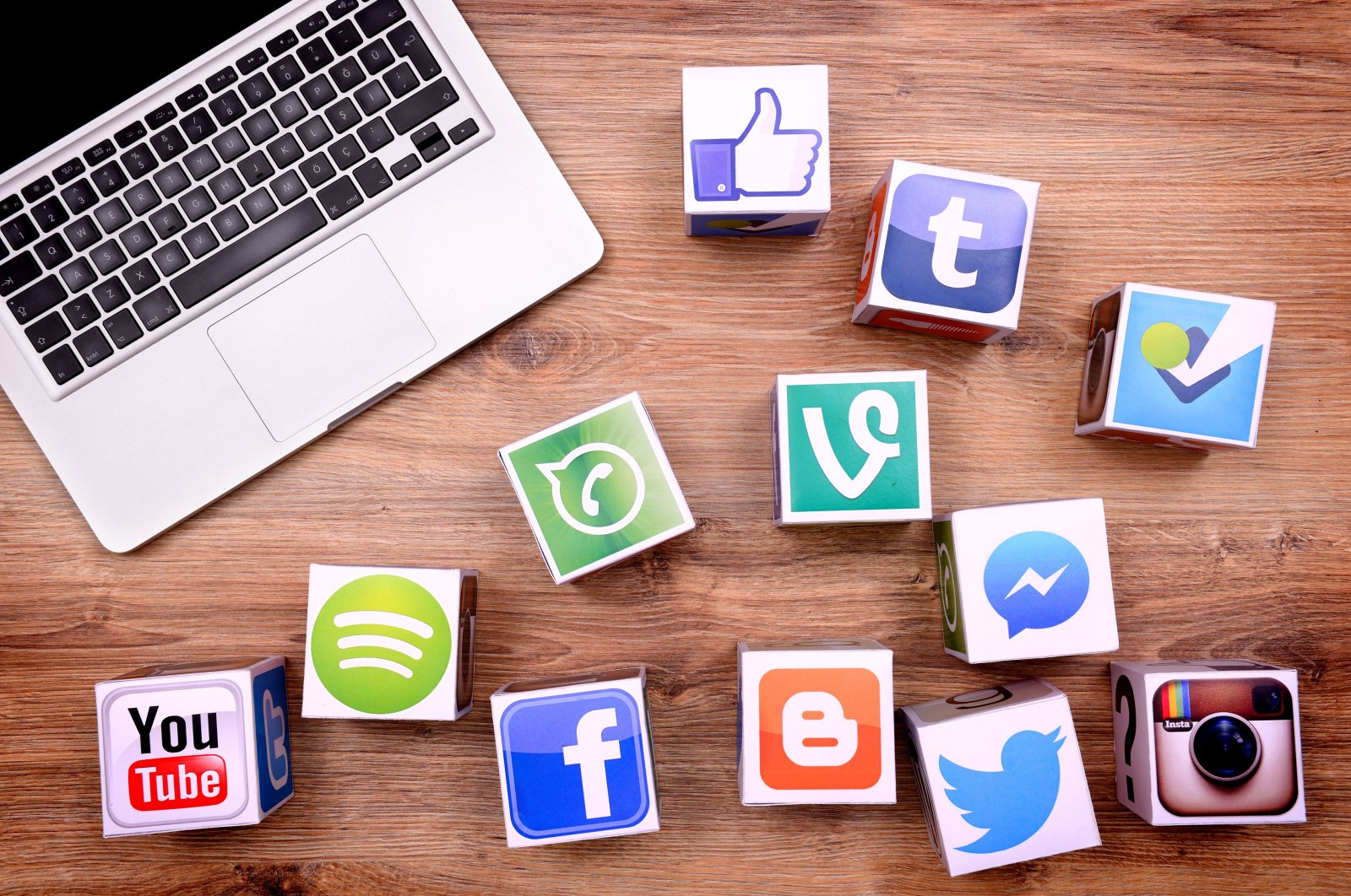 Paper cubes with popular social media services icons, including Facebook, Instagram, Youtube, Twitter, and a Macbook Pro laptop computer lay on a wooden desk. (Getty Images)