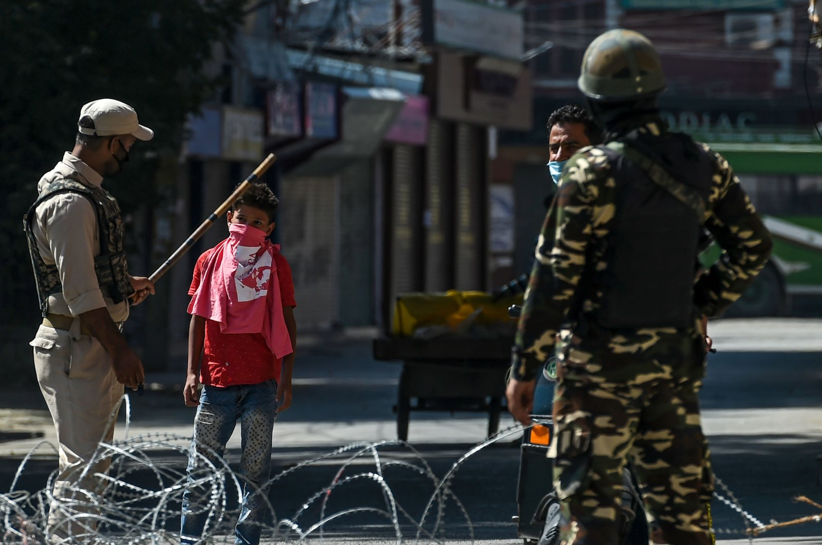 Security personnel stop pedestrians on a street during a lockdown imposed by the authorities as a preventive measure against the surge in COVID-19 coronavirus cases, in Srinagar, July 23, 2020. (AFP Photo)