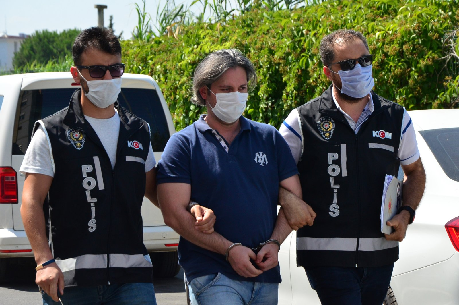 Former police captain Mustafa S. is escorted by officers after he turning himself in, Adana, Turkey, July 24, 2020. (DHA Photo)