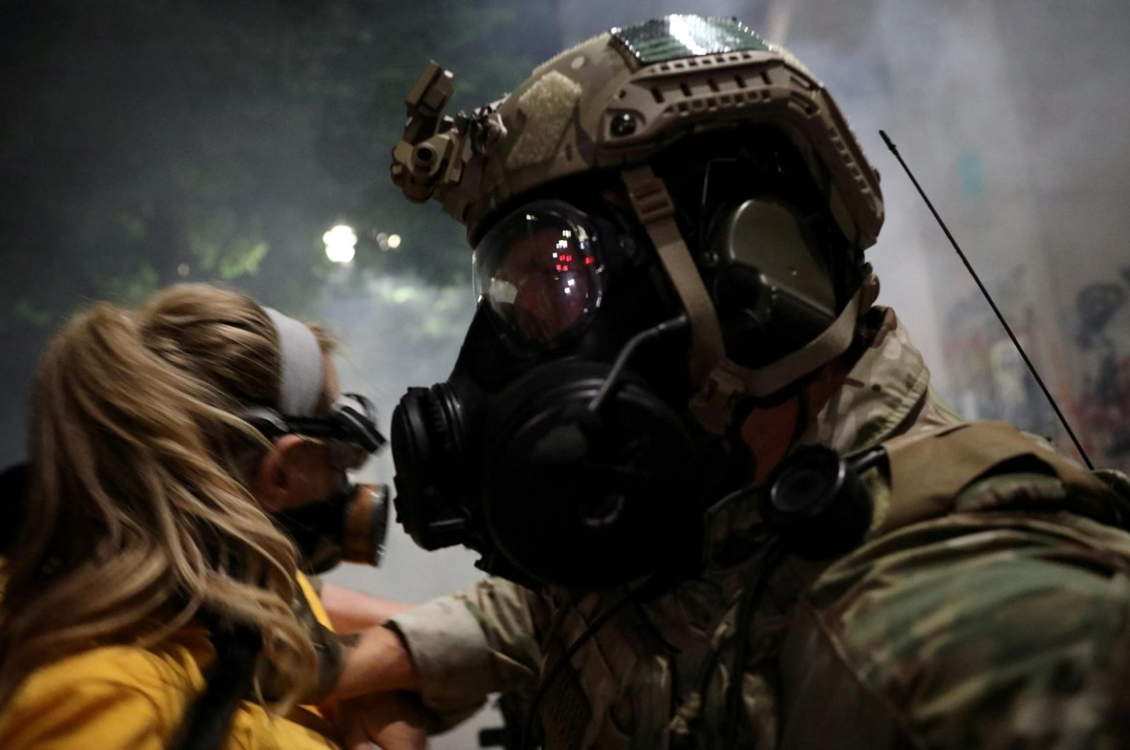A federal law enforcement officer pushes a mother back during a demonstration against the presence of federal law enforcement officers and racial inequality in Portland, Oregon, U.S., July 21, 2020. (Reuters Photo)