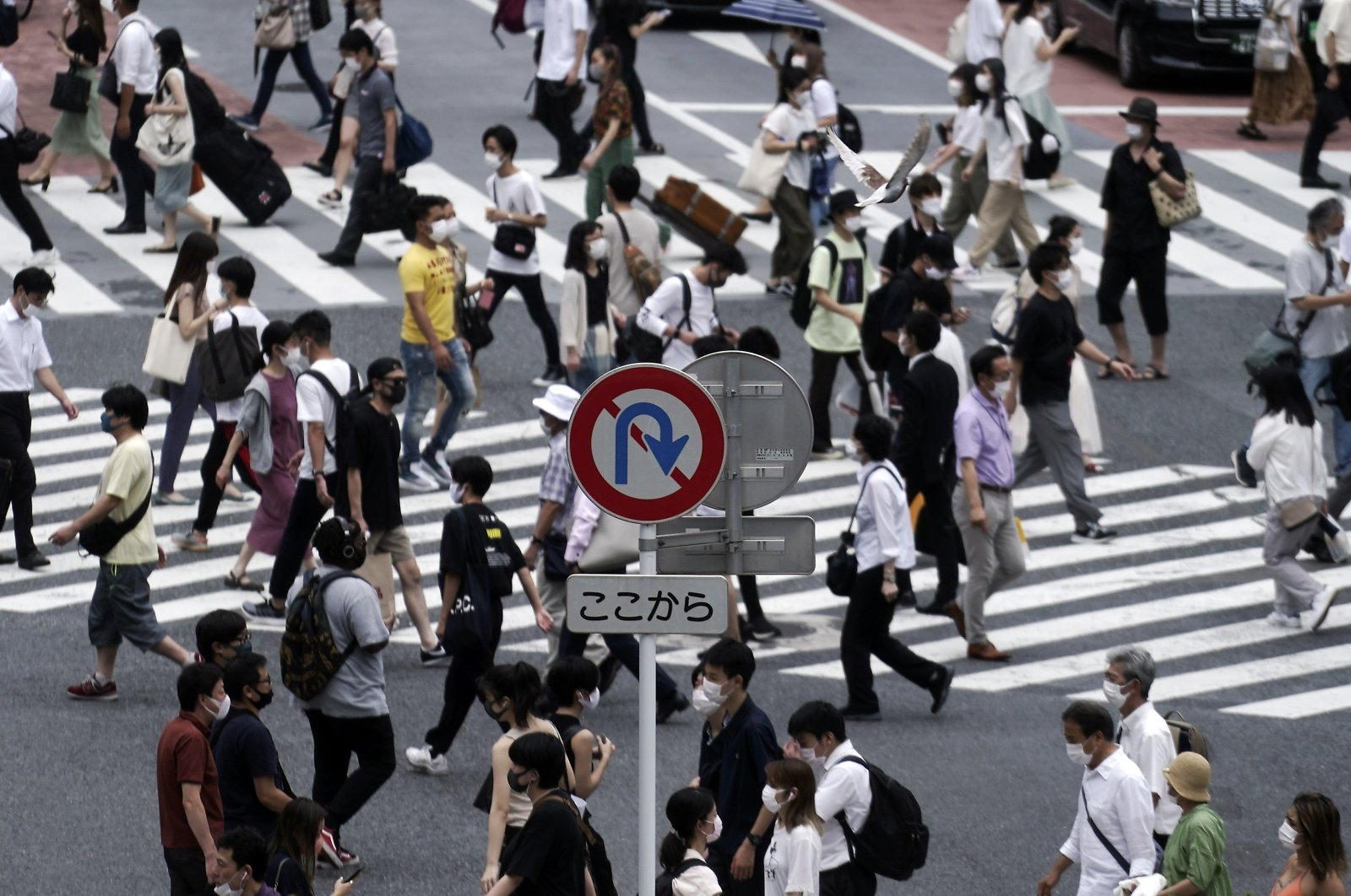 Near a No U Turn roads sign, people wearing masks against the spread of the new coronavirus walk at Shibuya pedestrian crossing in Tokyo Tuesday, July 21, 2020. (AP Photo)