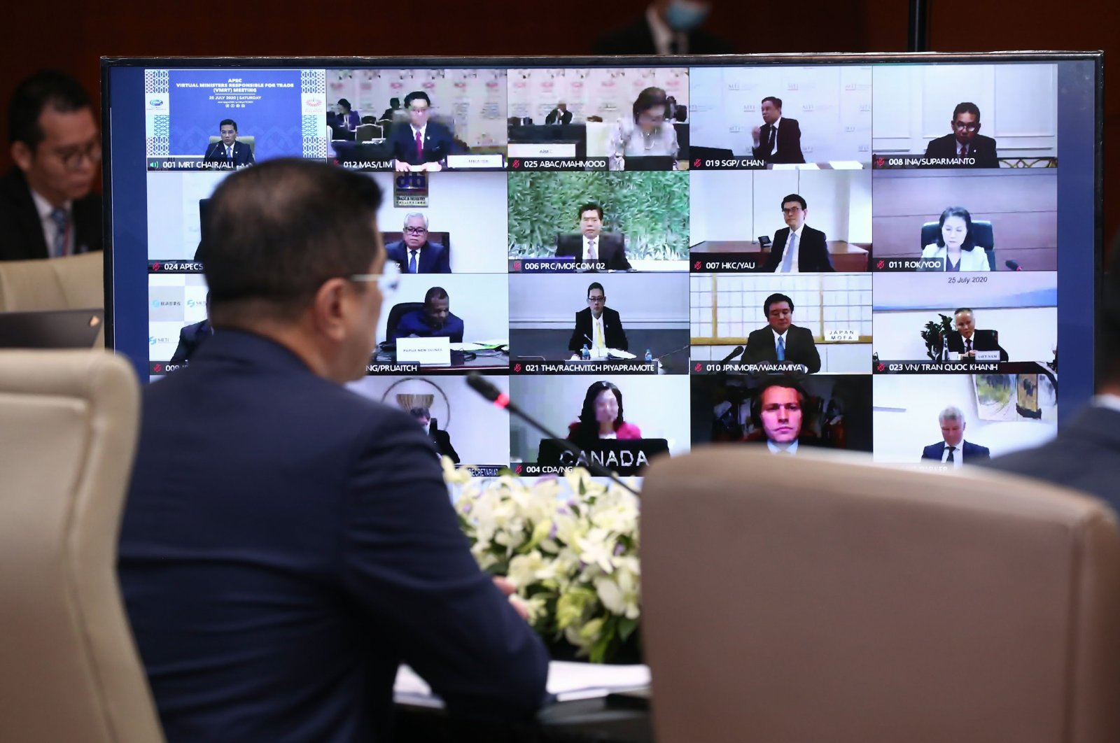 Mohamed Azmin Ali (L), Malaysia's Minister of International Trade and Industry, speaking before a monitor showing participants in the 2020 APEC Virtual Ministers Responsible for Trade Meeting on the COVID-19 coronavirus crisis in Kuala Lumpur, Malaysia on July 25, 2020. (AFP Photo)