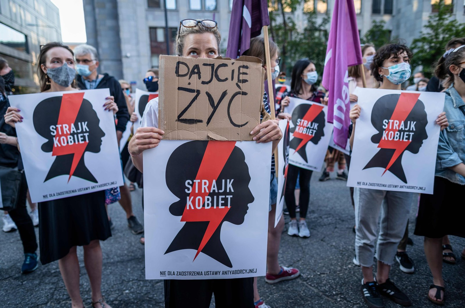 """Protesters hold banners reading """"Let us live"""" and """"Women's Strike"""" as they take part in protest against the Polish government plans to withdraw from the Istanbul Convention on prevention and combatting of home violence, in Warsaw, Poland on July 24, 2020. (AFP Photo)"""