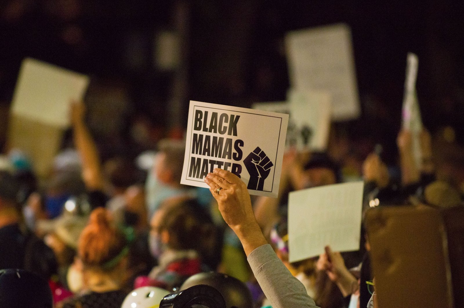 Activists hold up signs as they take part in a rally against police brutality in Portland, Oregon late on July 24, 2020. (AFP Photo)