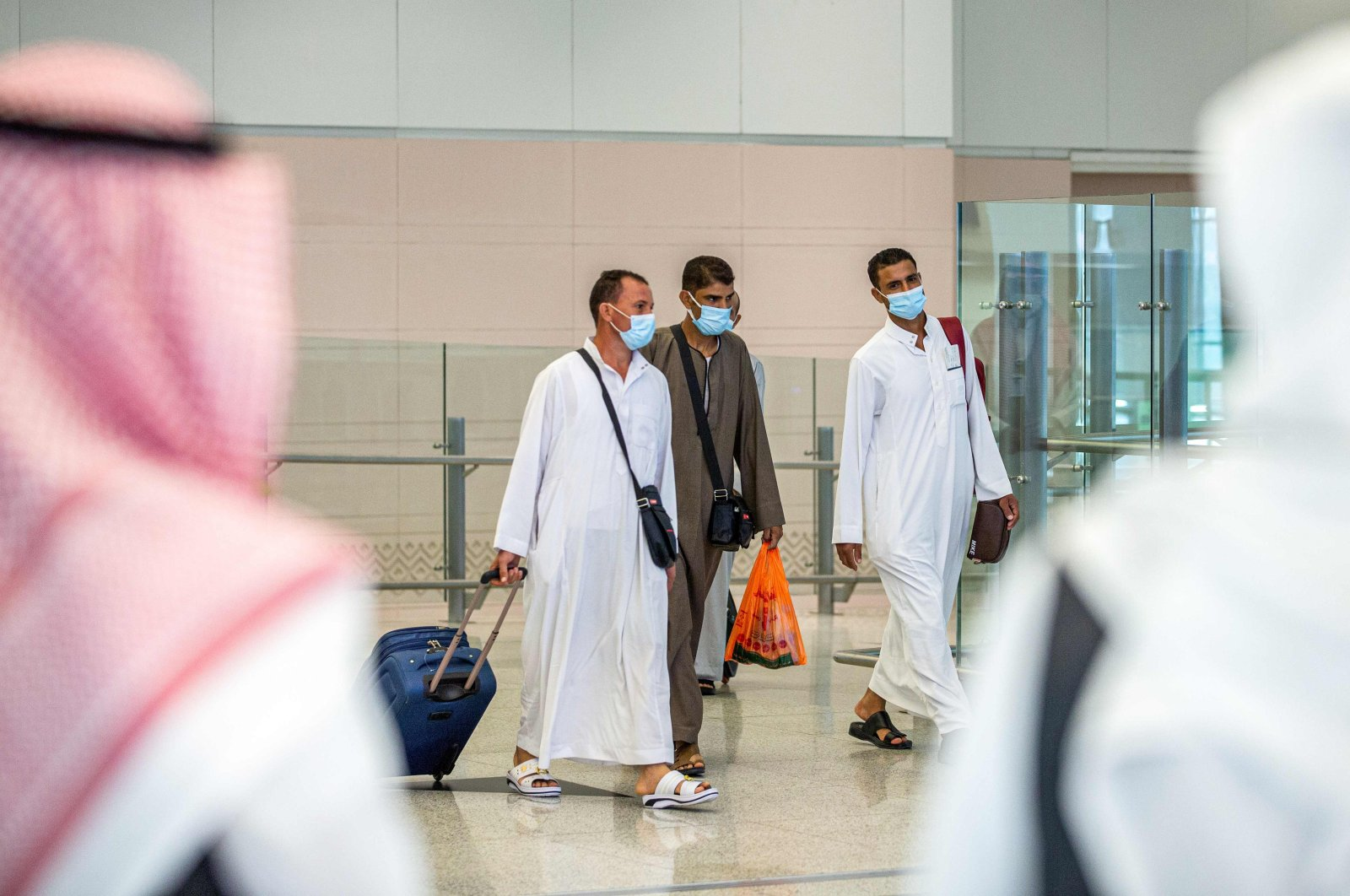 A handout picture provided by the Saudi Ministry of Hajj and Umra on July 25, 2020, shows travellers, mask-clad due to the COVID-19 coronavirus pandemic, walking with luggage as part of the first group of arrivals for the annual Hajj pilgrimage, at the Red Sea coastal city of Jeddah's King Abdulaziz International Airport.(AFP Photo)