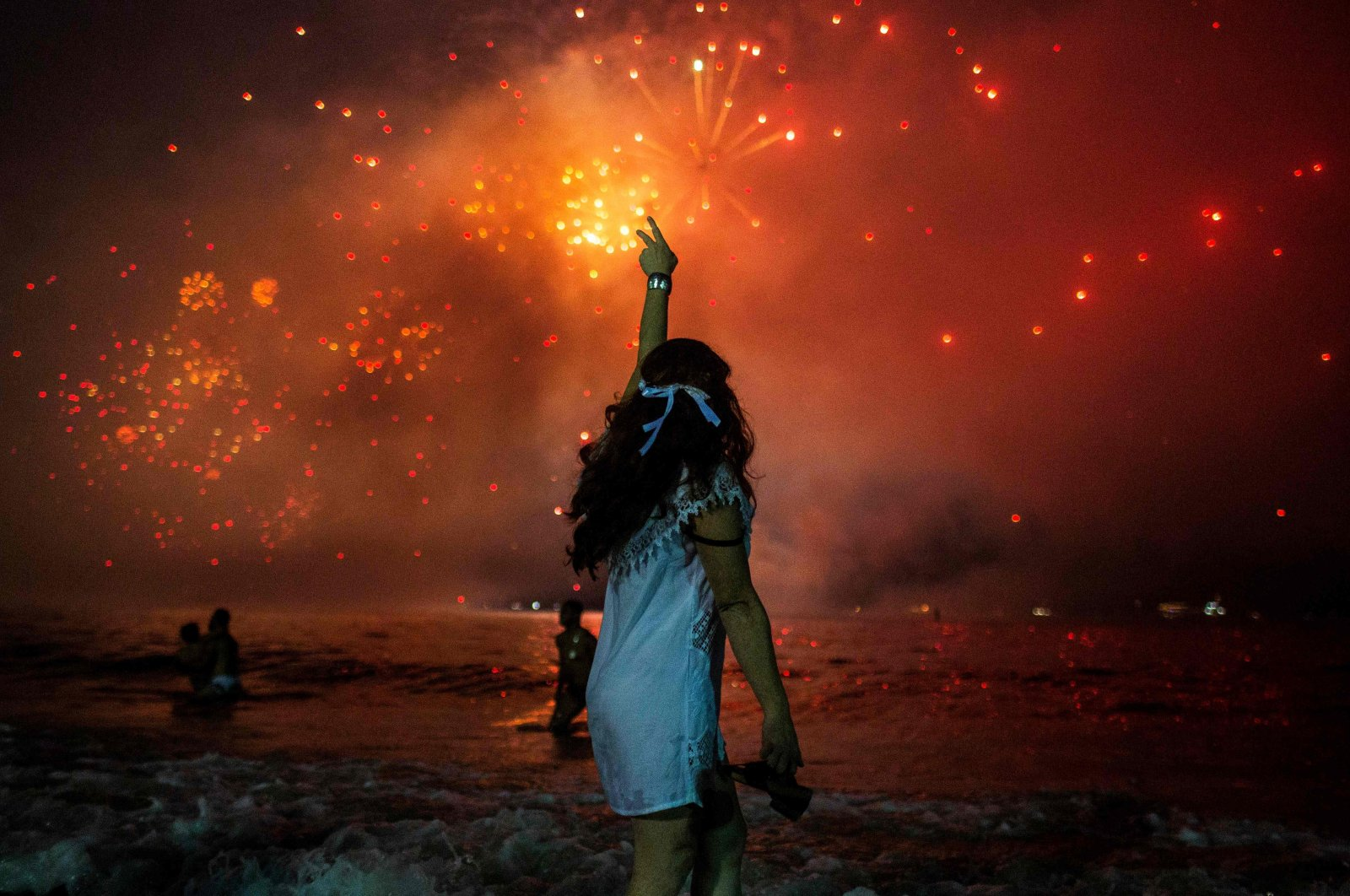 In this file picture taken on December 31, 2019 a woman celebrates as she watches the traditional New Year's fireworks at Copacabana Beach in Rio de Janeiro, Brazil. (AFP Photo)