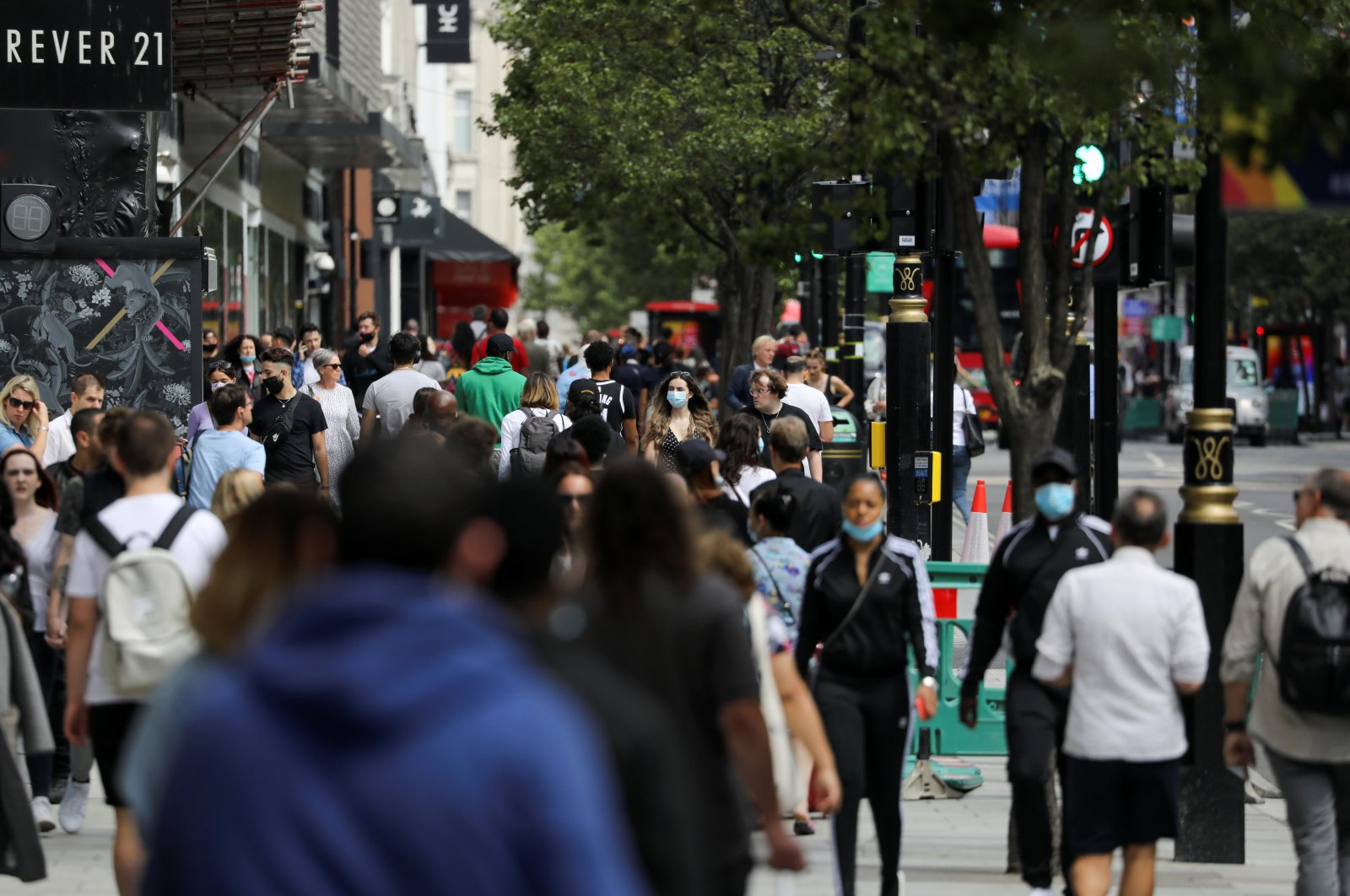 People, some of them wearing protective masks, walk down Oxford Street as the spread of the coronavirus disease (COVID-19) continues, in London, Britain July 24, 2020. (REUTERS Photo)