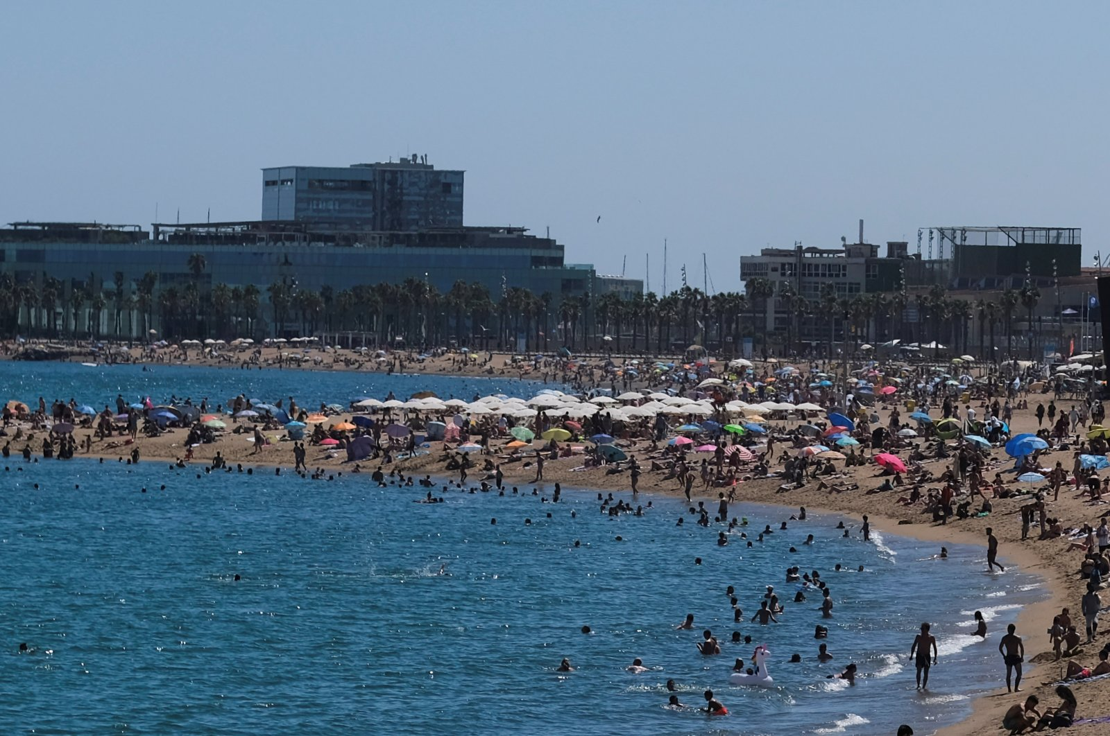 People enjoy the sunny weather at the Barceloneta beach, after Catalonia's regional authorities and the city council announced restrictions to contain the spread of the coronavirus disease (COVID-19) in Barcelona, Spain, July 19, 2020. (REUTERS Photo)
