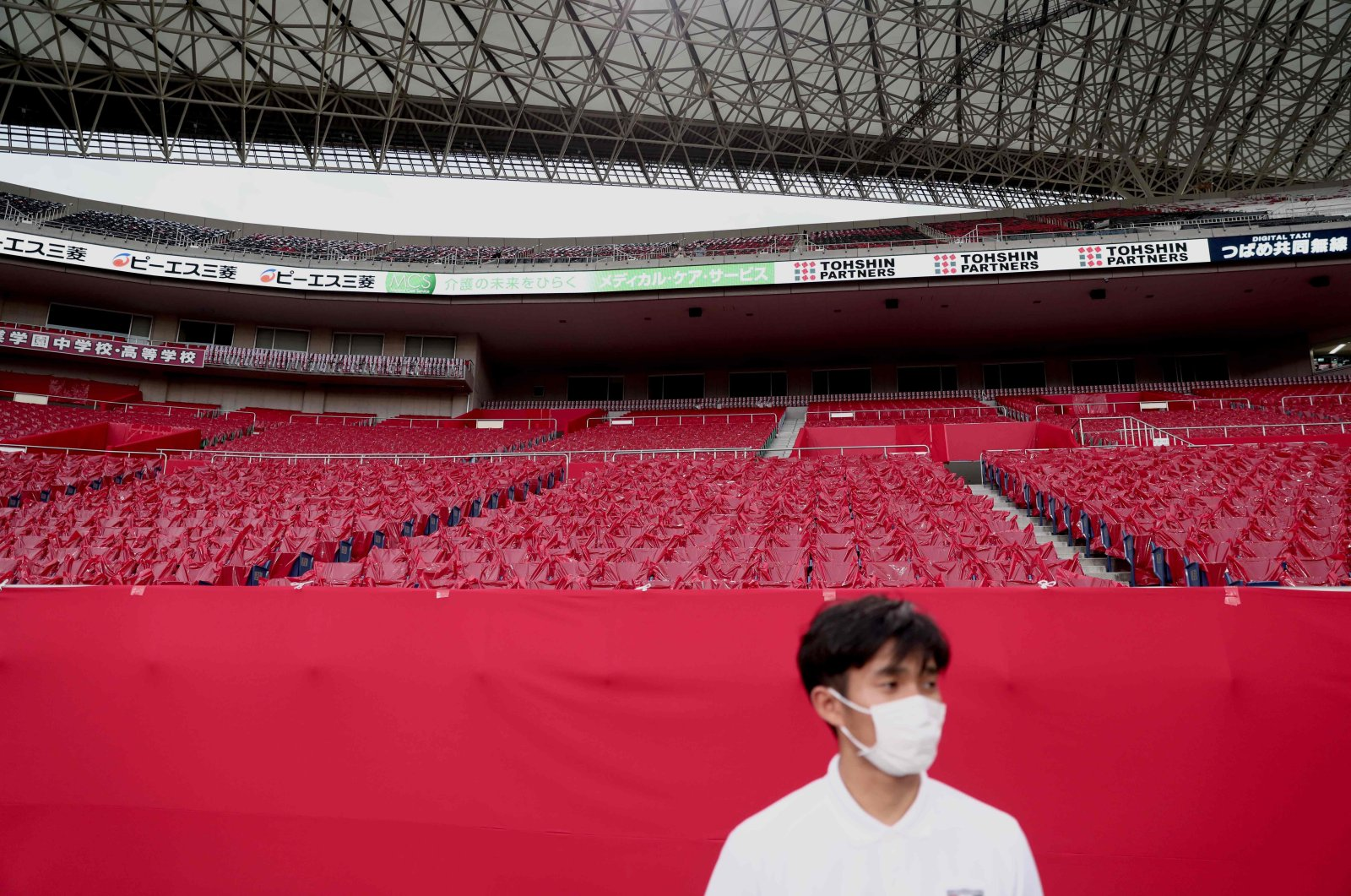 An employee wearing a face mask stands in front of empty seats before the start of the J-League football match between Urawa Reds and Yokohama F. Marinos in Saitama, Japan, July 4, 2020. (AP Photo)