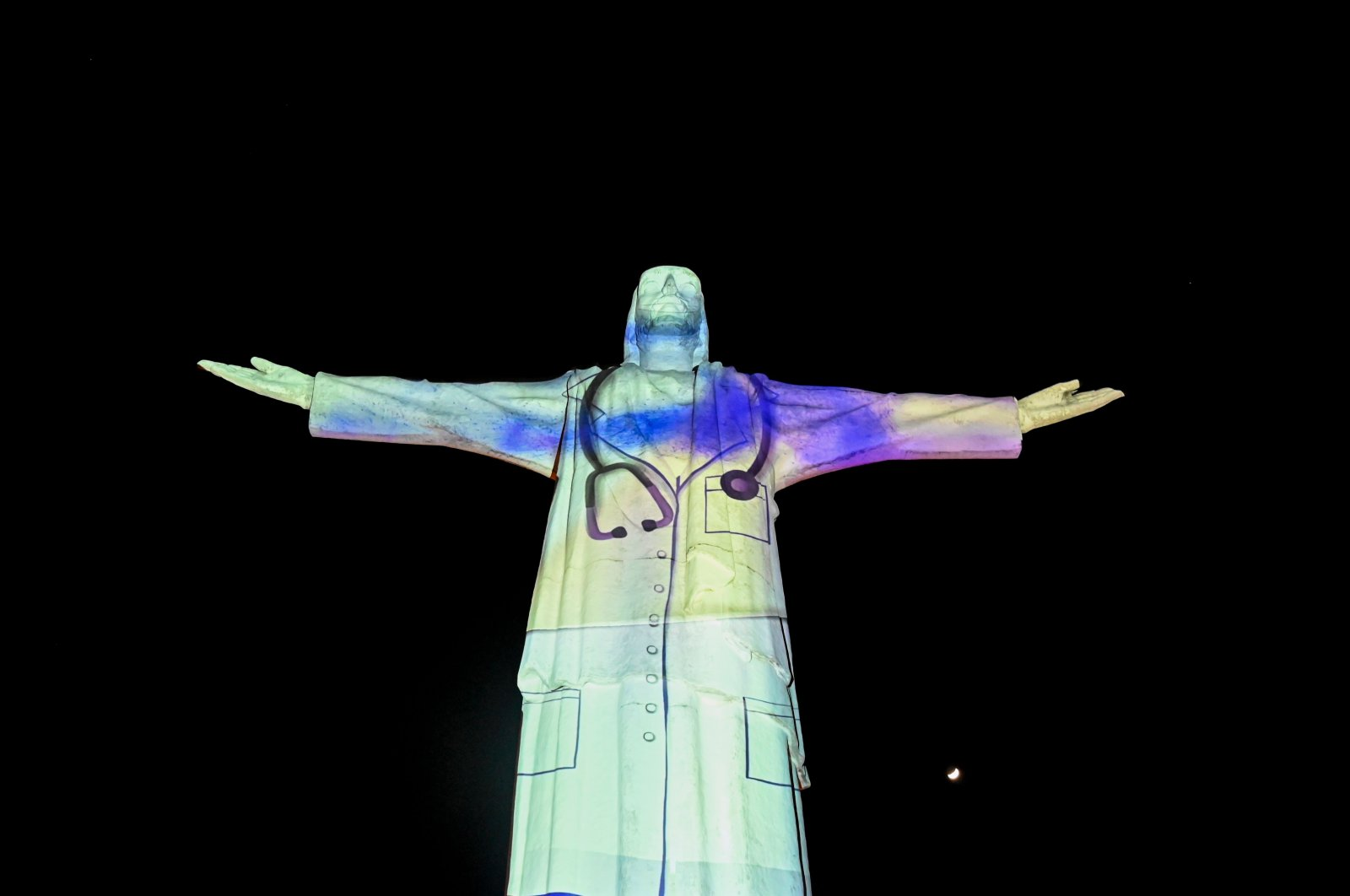 The image of a doctor is projected on the statue of Cristo Rey monument in Cali, Colombia, during celebrations for the 484th anniversary of the city, on July 25, 2020.(AFP Photo)