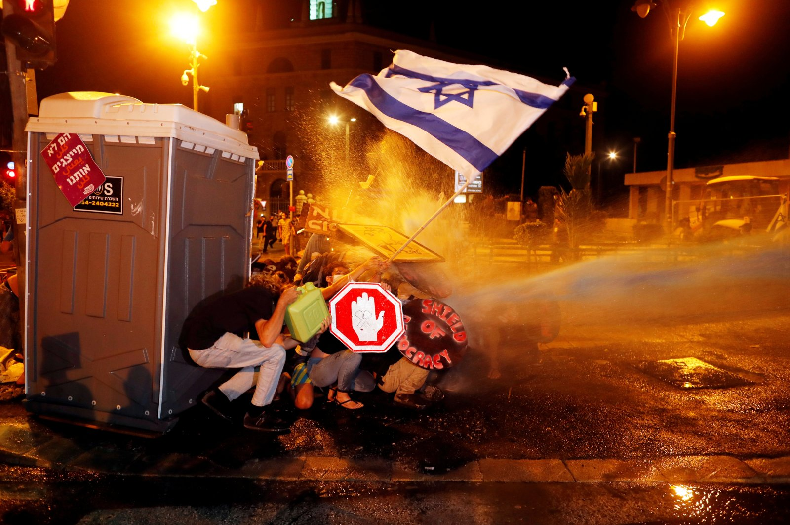 Police use water cannons during a protest against Israeli Prime Minister Benjamin Netanyahu's alleged corruption and his government's handling of the coronavirus crisis, near his residence in Jerusalem on July 26, 2020. (Reuters Photo)