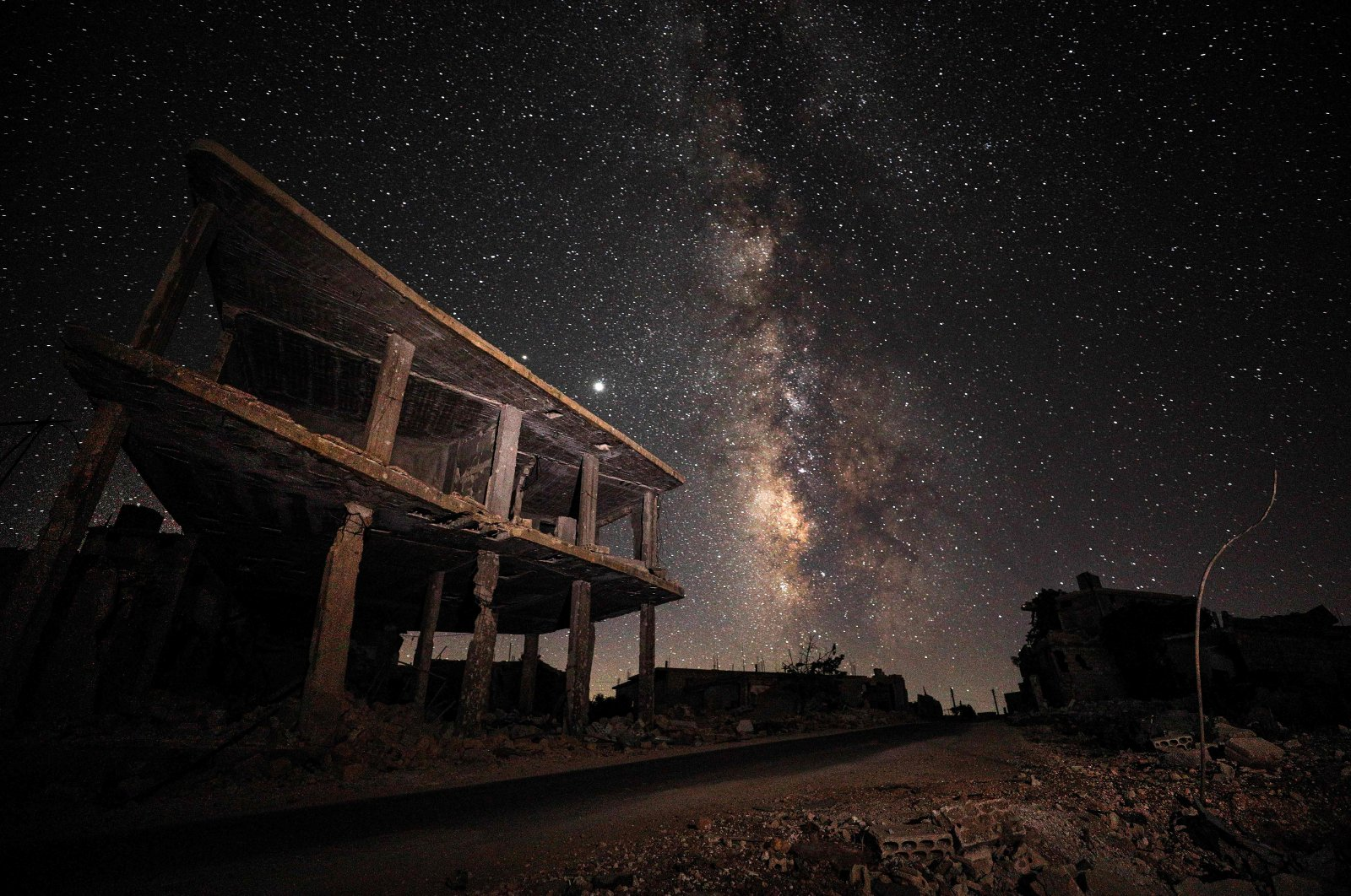 This long-exposure picture shows a view of the Milky Way galaxy rising in the sky above destroyed buildings in the village of Balyun in the opposition-held southern countryside of Syria's northwestern province of Idlib, near the frontline with government forces, July 21, 2020. (AFP Photo)