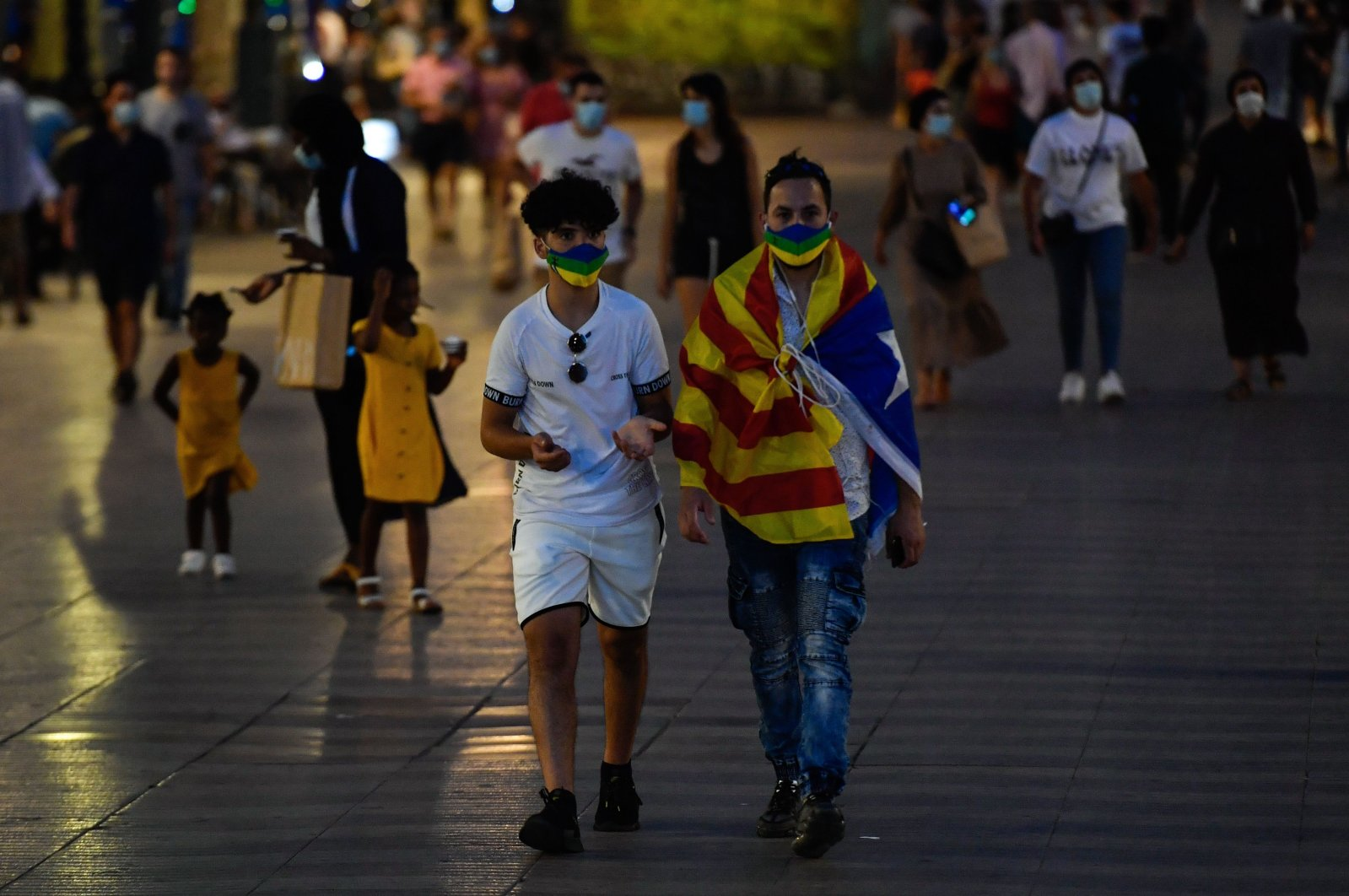 """A man wrapped in a Catalan pro-independence """"Estelada"""" flag walks on Las Ramblas street in Barcelona on July 25, 2020. (AFP Photo)"""