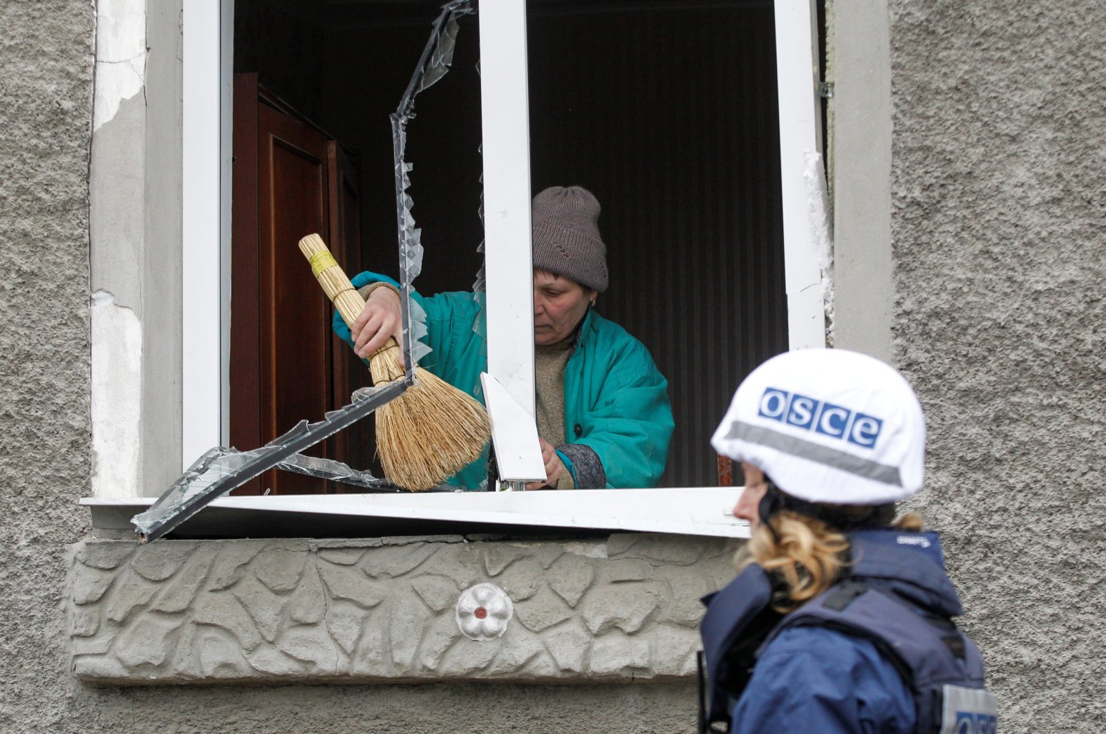A member of the Organization for Security and Co-operation in Europe (OSCE) walks past a local resident removing debris from inside a house damaged during fighting between the armed forces of Ukraine and the separatist Lugansk People's Republic in the settlement of Holubivske, the Luhansk region, Ukraine, Feb. 19, 2020. (Reuters Photo)