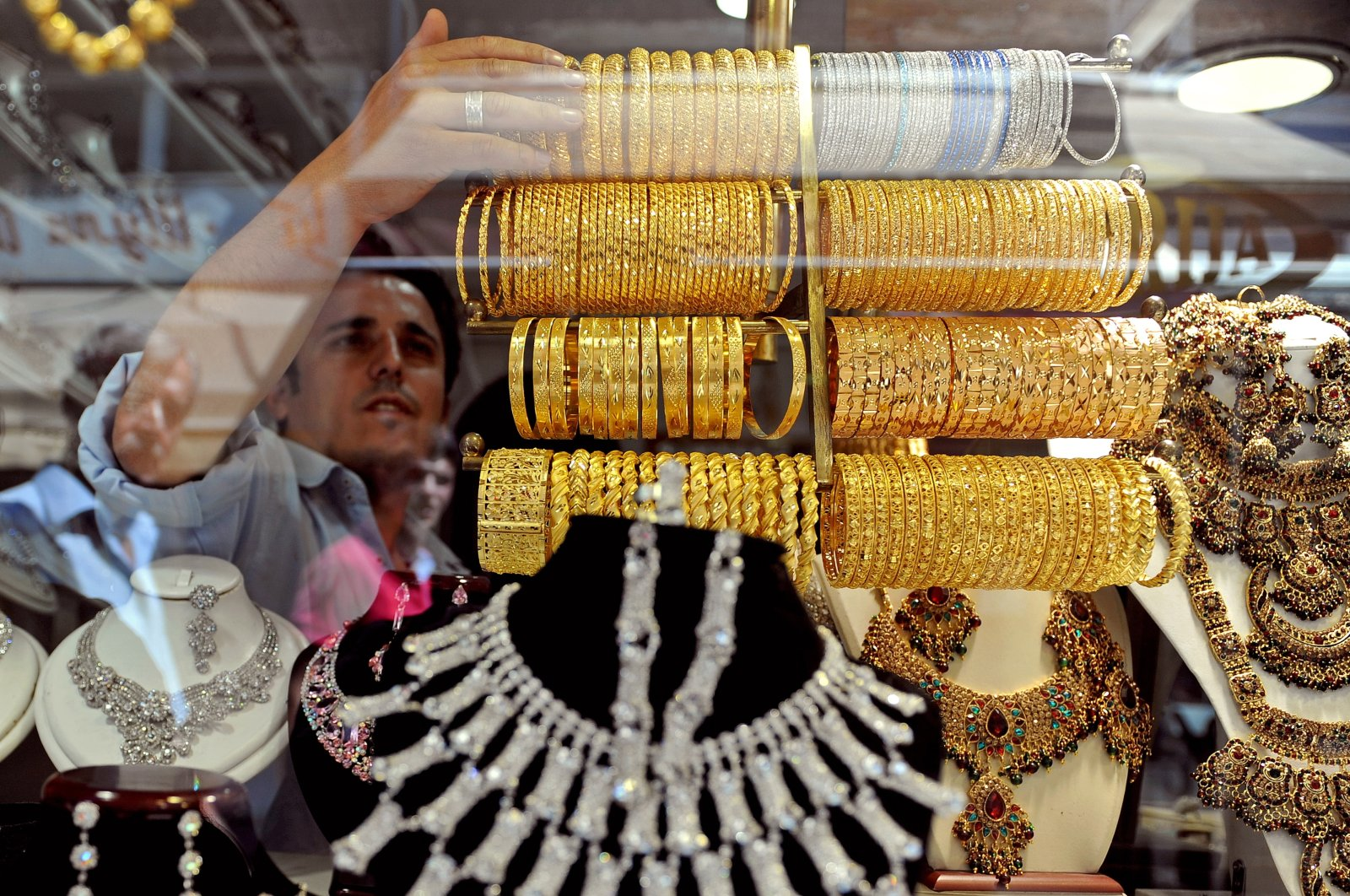 A jewelry worker sets up his shop showcase in one of the many gold jewelry shops in the old Turkish bazaar in Skopje, North Macedonia, Aug. 19, 2011. (EPA Photo)