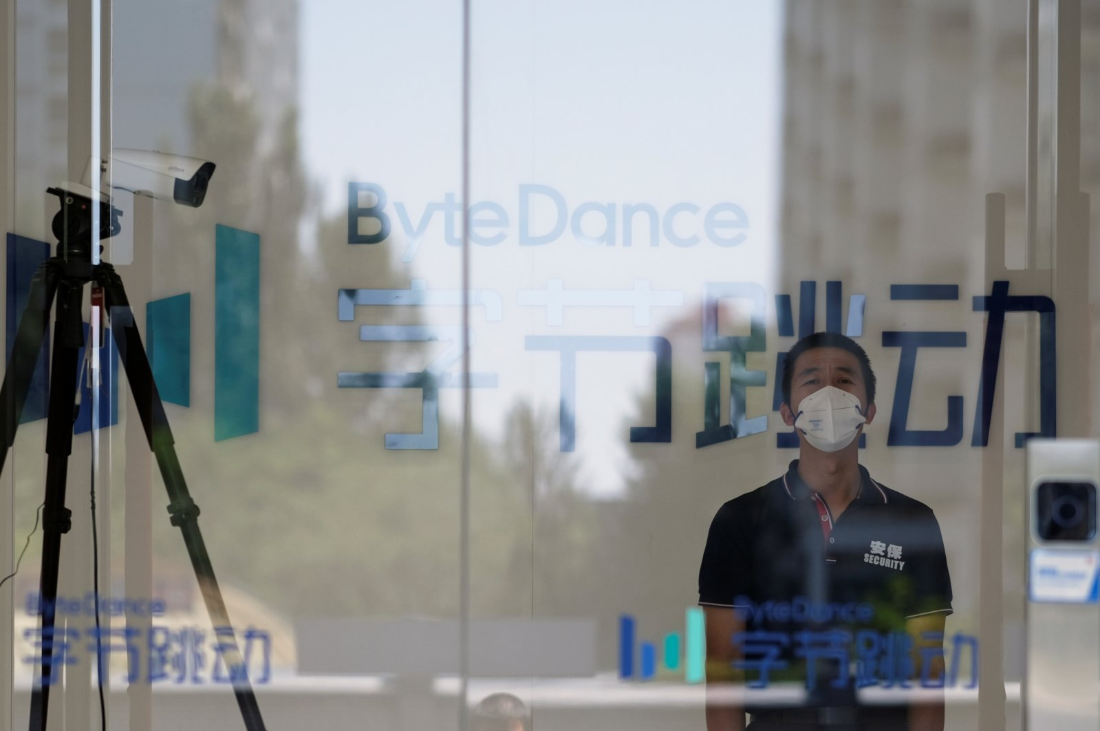 A security guard, wearing a face mask to protect against the coronavirus, stands near a surveillance camera at an office of Bytedance, the China-based company which owns the short video app TikTok, in Beijing, China, July 7, 2020. (Reuters Photo)