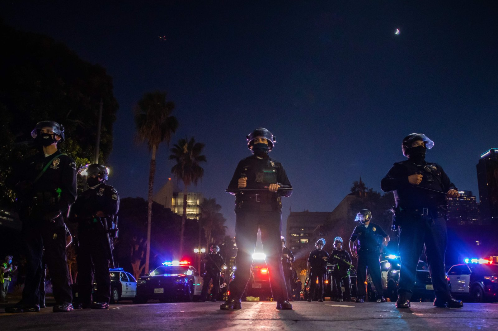 Police officers hold a line in front of LA City Hall during a protest demanding justice for George Floyd, Breonna Taylor and also in solidarity with Portland's protests, in Downtown Los Angeles, California, July 25, 2020. (AFP Photo)