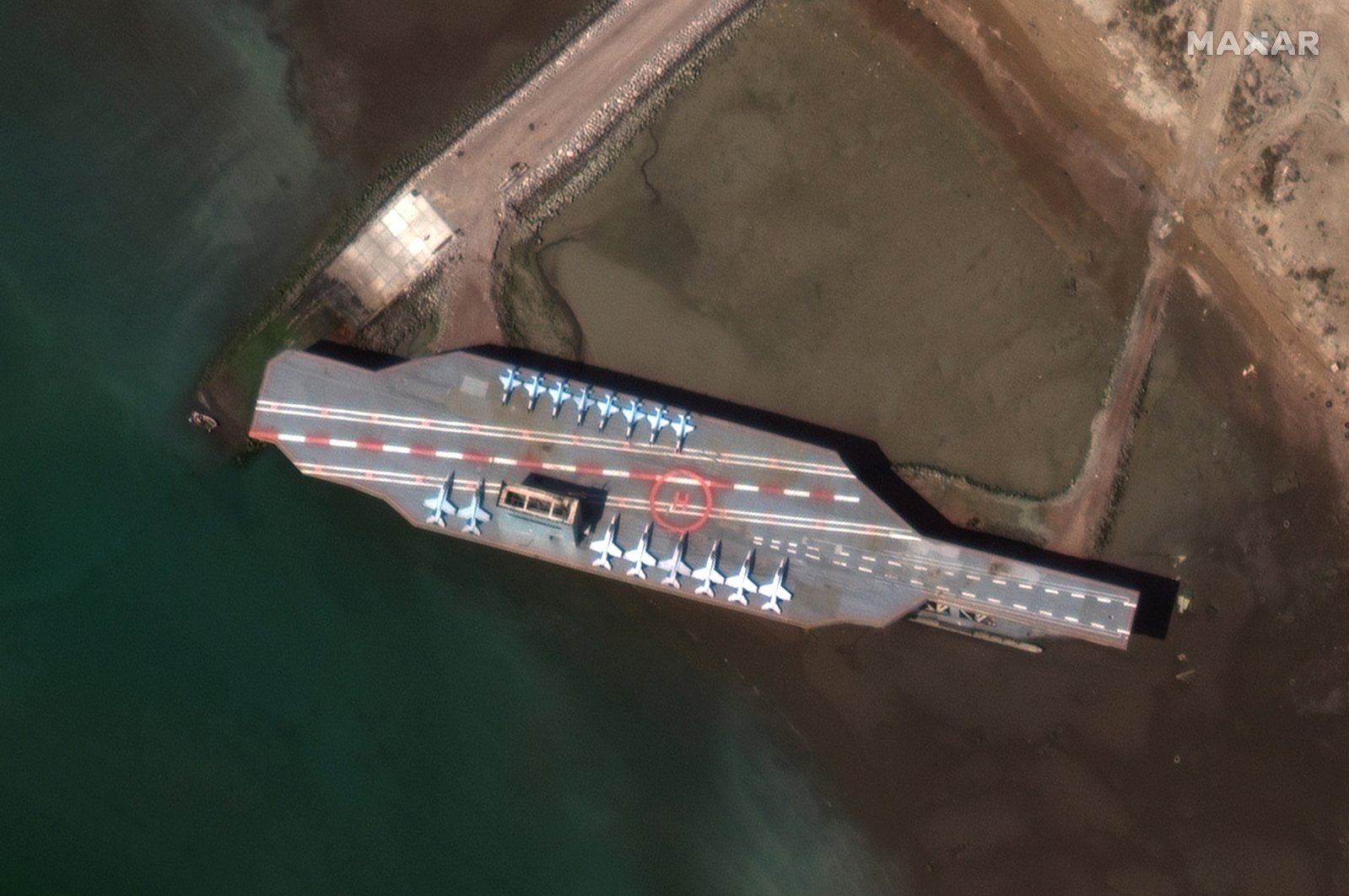 Iran's refurbished mock-up aircraft carrier, used previously as a simulated U.S. target during a February 2015 Iranian naval war games exercise, is seen at its homeport of Bandar Abbas, Iran, Feb.y 15, 2020. ( Satellite image ©2020 Maxar Technologies Photo via Reuters)