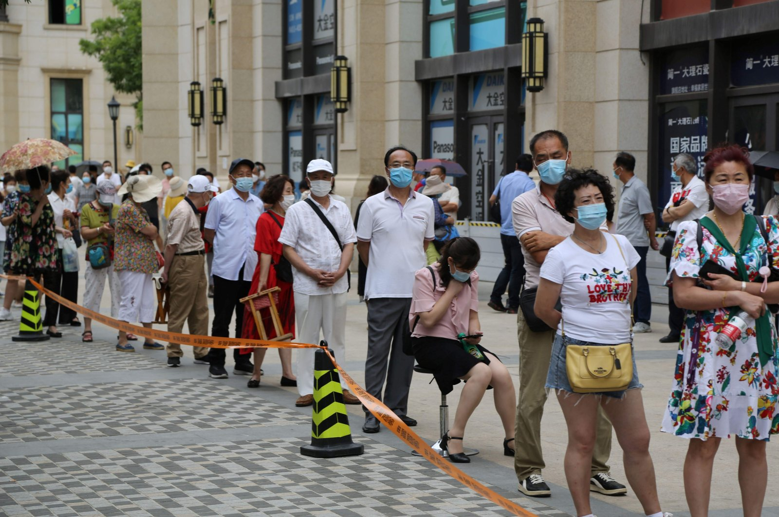 People line up to undergo COVID-19 tests at a makeshift testing center in Dalian, in China's northeast Liaoning province, July 27, 2020. (AFP Photo)