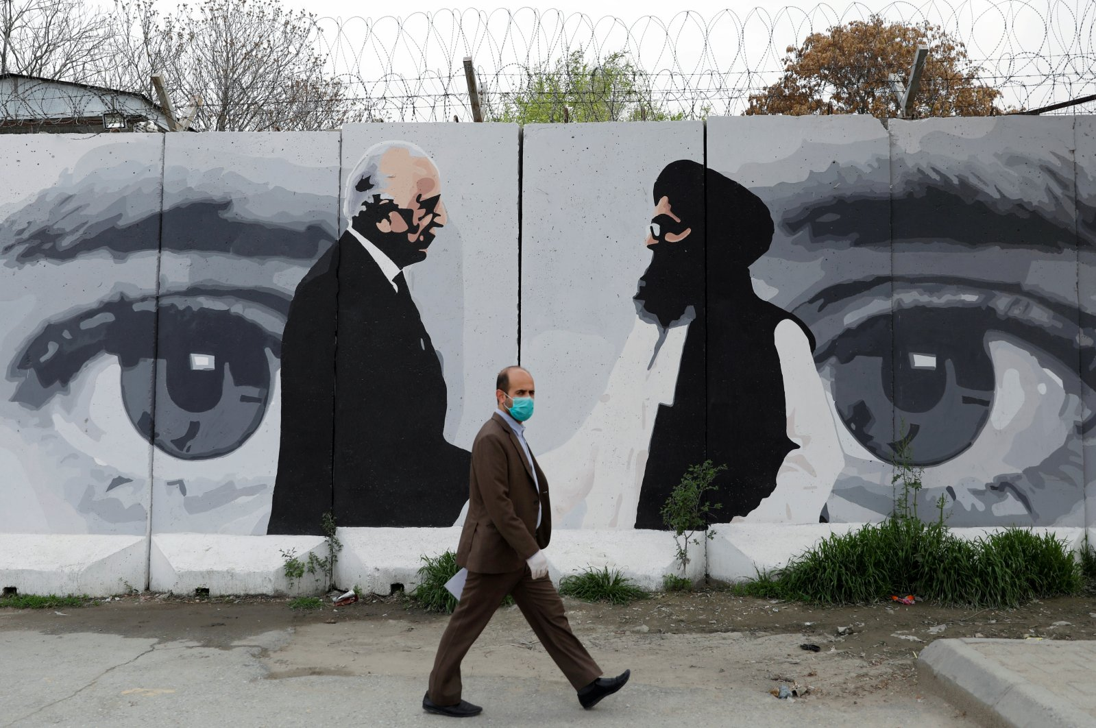 An Afghan man wearing a protective face mask walks past a wall painted with a photo of Zalmay Khalilzad, the U.S. envoy for peace in Afghanistan, and Mullah Abdul Ghani Baradar, the leader of the Taliban delegation, Kabul, April 13, 2020. (REUTERS Photo)