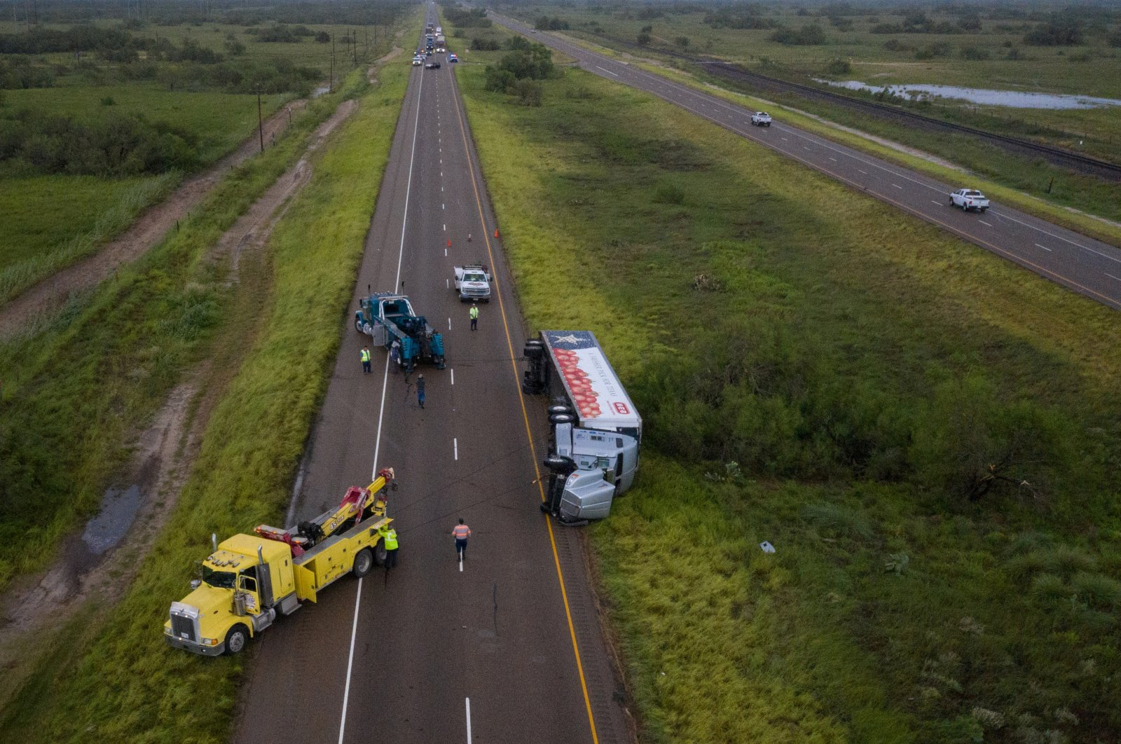 Traffic is halted as tow trucks surround an overturned HEB supermarket truck along U.S. Route 77 in the aftermath of high wind gusts from Hurricane Hanna in Sarita, Texas, U.S., July 26, 2020. (Reuters Photo)