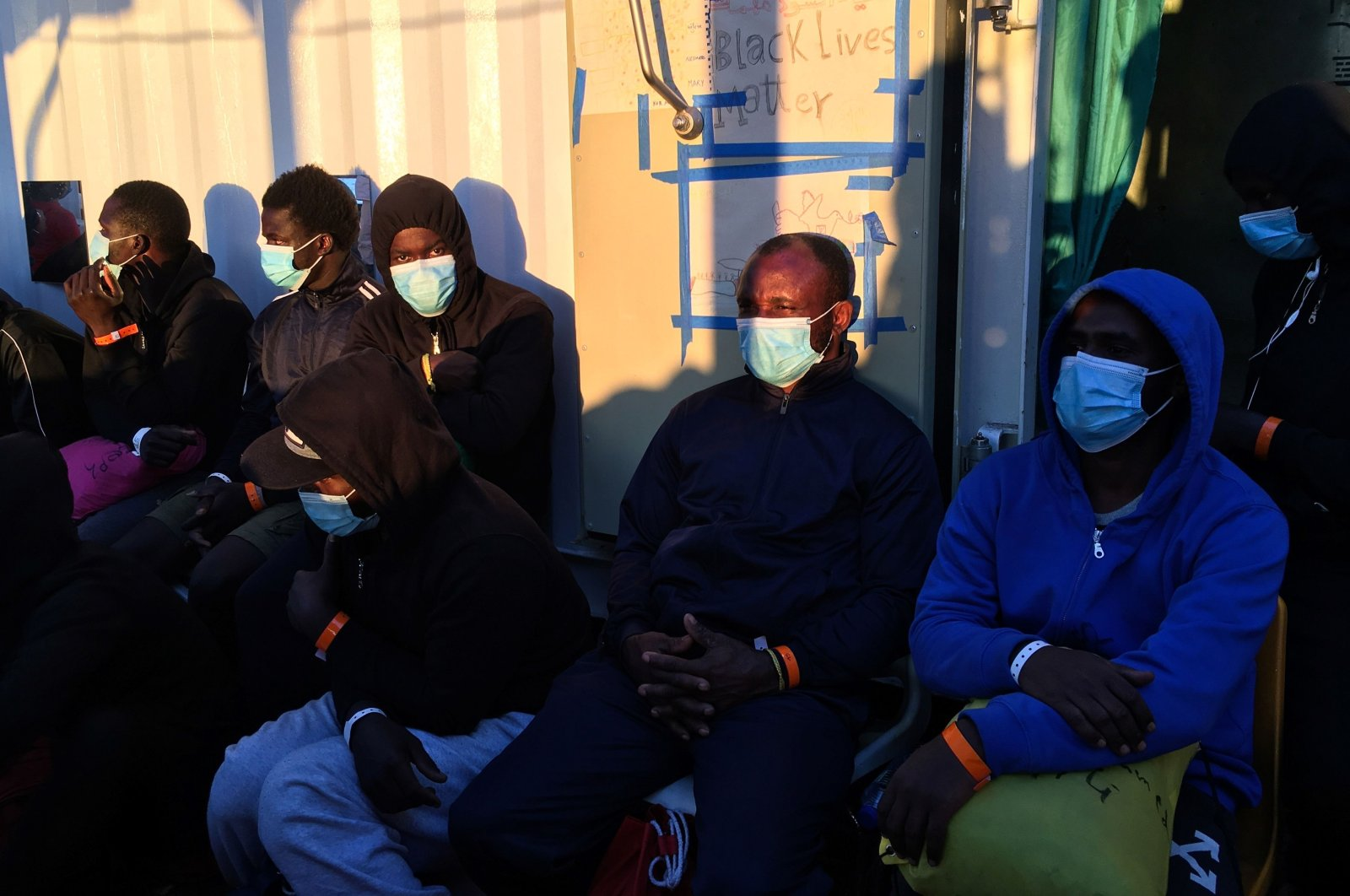 Migrants wearing protective facemasks on board of the humanitarian aid boat Ocean Viking, chartered by charity group SOS Mediterranee, prepare to disembark upon their arrival on July 6, 2020.