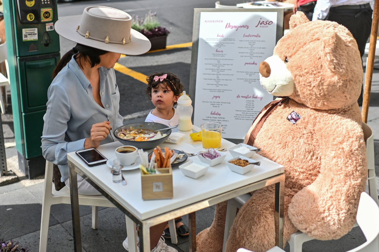 Customers sit with a teddy bear used to maintain a social distance during the coronavirus pandemic at a restaurant in Polanco neighborhood, in Mexico City, July 26, 2020. (AFP Photo)