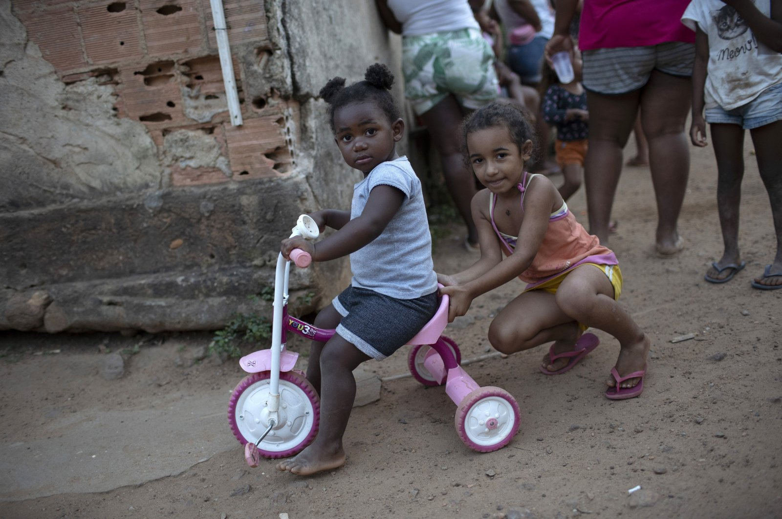 Children play as the adults collect donated food, cleaning supplies and protective face masks on the outskirts of Rio de Janeiro, July 12, 2020. (AP Photo)