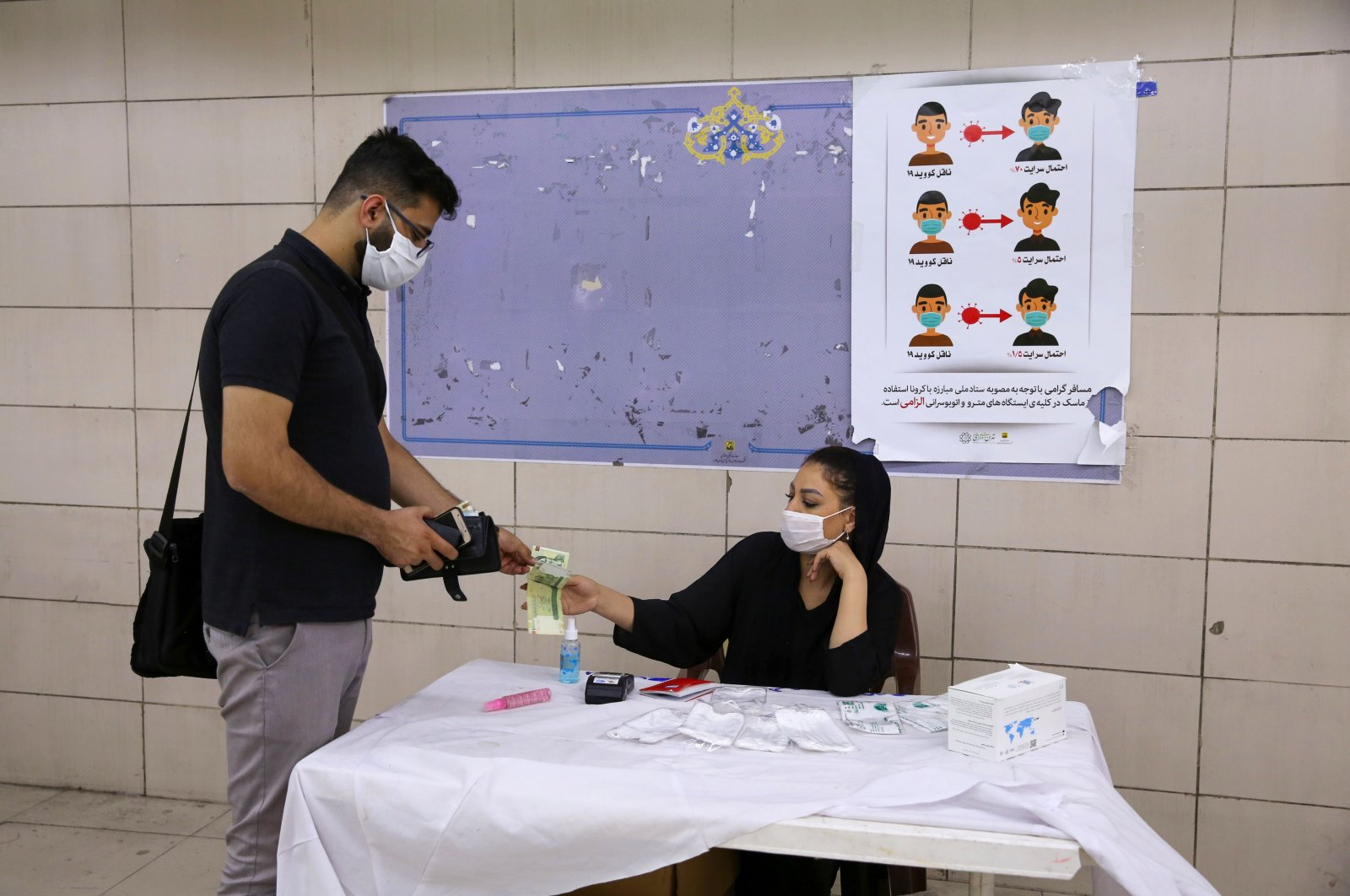 An Iranian man wearing a protective face mask buys hand sanitizer from a woman at a metro station during the COVID-19 pandemic, in the capital Tehran, Iran, July 22, 2020. (AFP Photo)