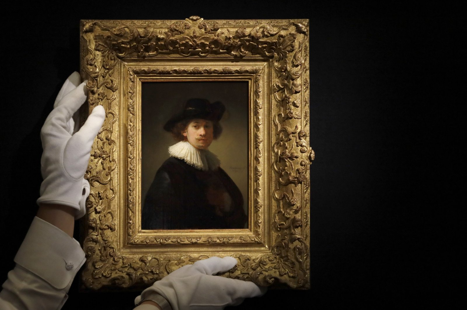 """A Sotheby's employee adjusts a painting by Rembrandt Van Rijn called """"Self-portrait, wearing a ruff and black hat"""" at Sotheby's auction rooms in London, Britain, July 23, 2020. (AP Photo)"""