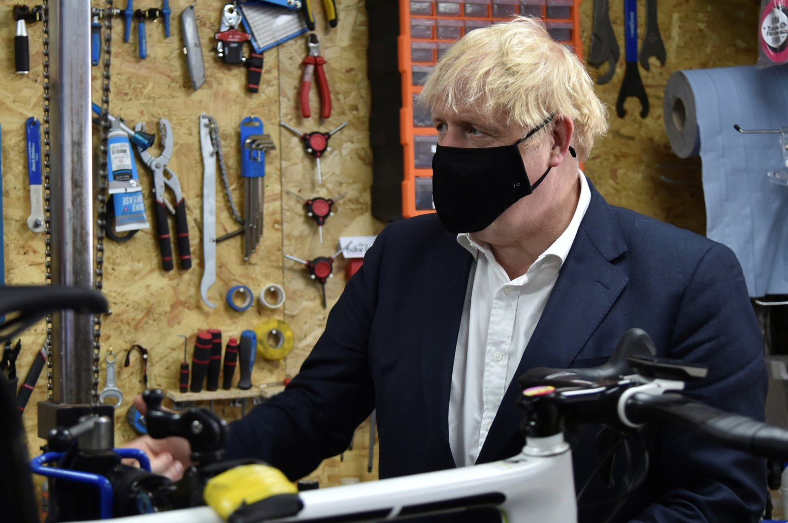 Britain's Prime Minister Boris Johnson talks to the owner of the the Cycle Lounge, Rodney Rouse, a bicycle repair shop, after the government announced a new plan to get Britain cycling, amid the outbreak of the coronavirus, in Beeston near Nottingham, Britain, July 28, 2020. (Reuters Photo)