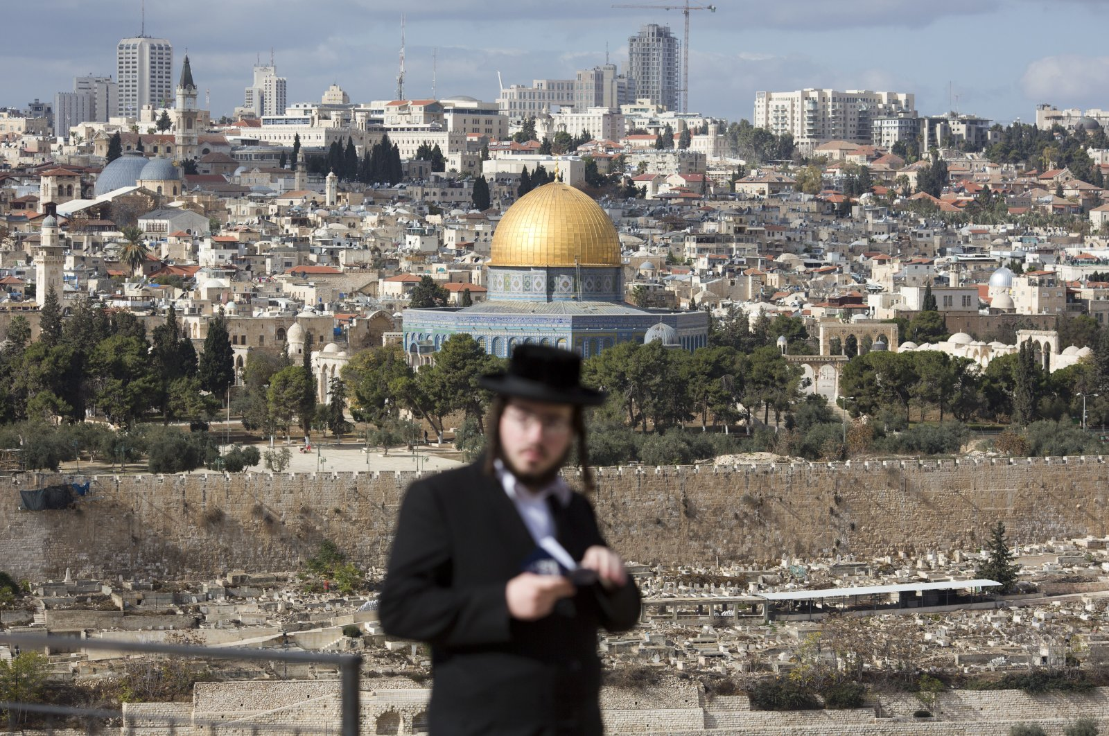 An orthodox Jewish man reads from a holy book in a cemetery near the Dome of the Rock Mosque in the Al Aqsa Mosque compound in Jerusalem's Old City, Thursday, Dec. 7, 2017. (AP Photo)
