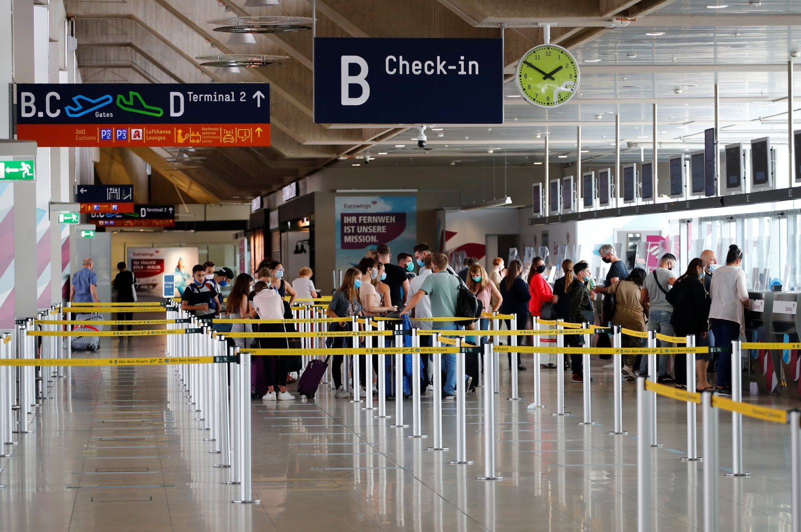 Travelers line up at a check-in counter of the Cologne-Bonn Airport, as the spread of the coronavirus disease (COVID-19) continues, in Cologne, Germany, July 28, 2020. (Reuters Photo)