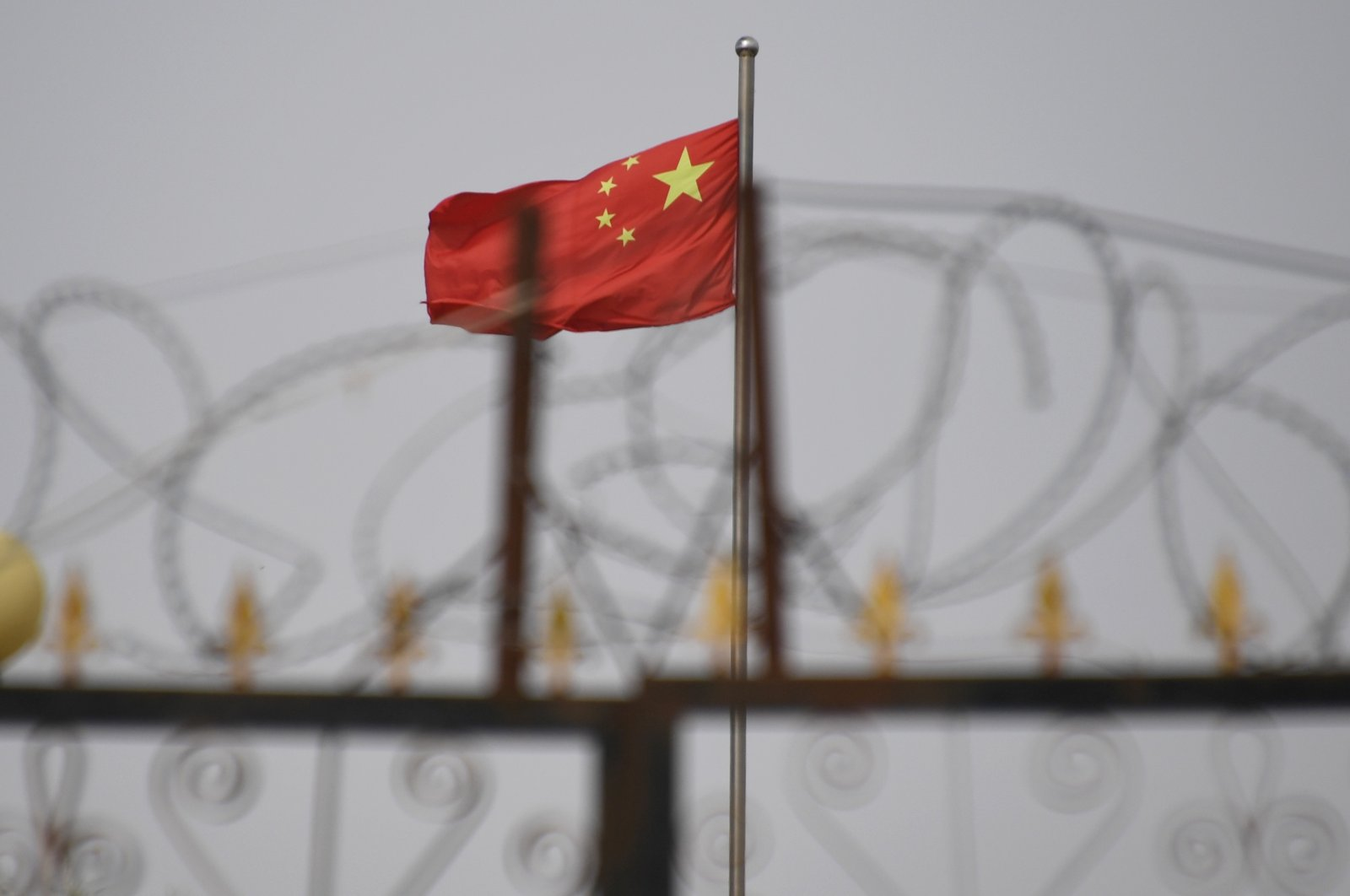 In this June 4, 2019, file photo, a Chinese flag is seen behind razor wire at a housing compound in Yangisar, south of Kashgar, in western Xinjiang region, China. (Badung Police via AFP)