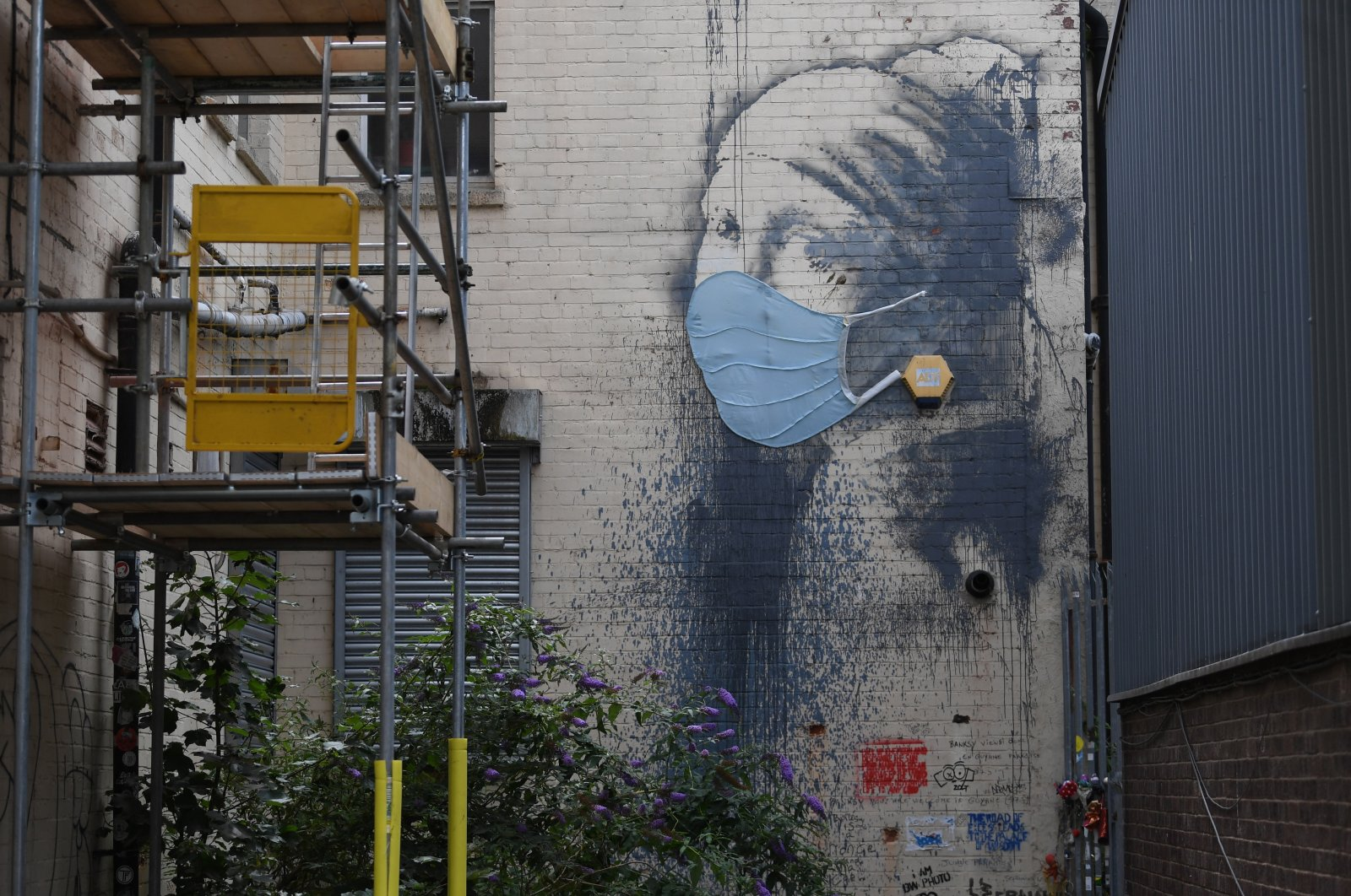 British artist Banksy's work 'Girl with a Pierced Eardrum' is displayed wearing a face covering in Bristol, UK, July 15, 2020. (EPA Photo)