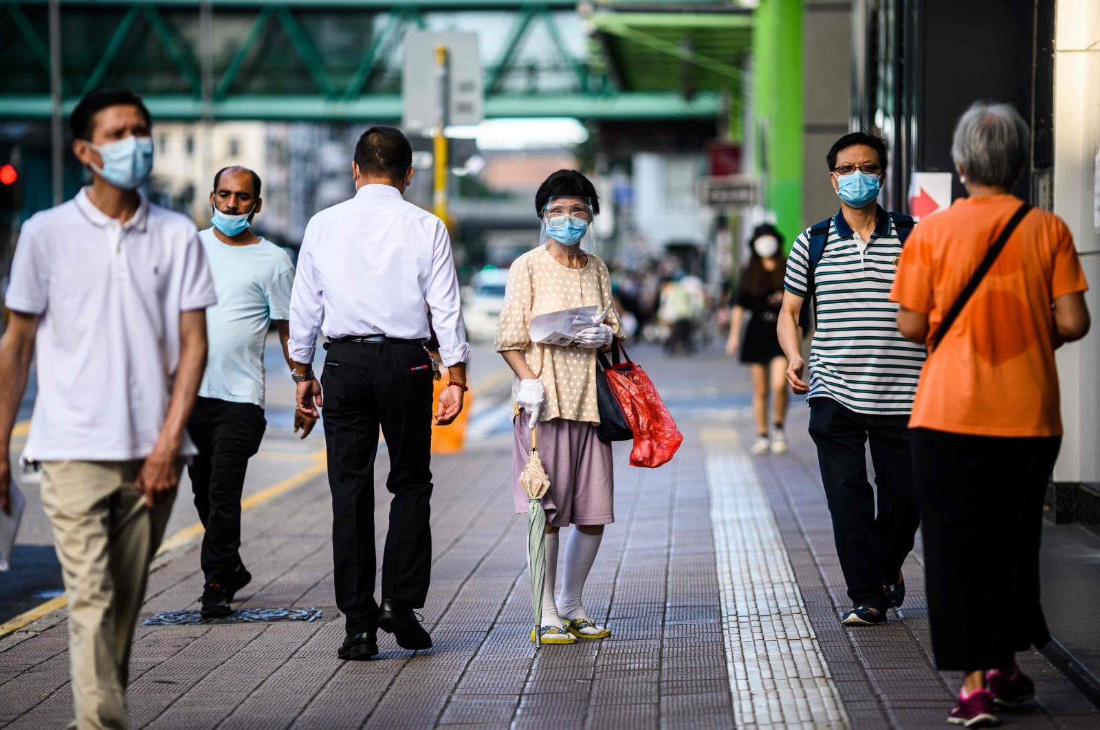 Pedestrians wear face masks in the Kowloon-side Sham Shui Po district of Hong Kong as new social distancing measures come into effect, which include having to wear masks in public to combat a new wave of coronavirus infections, China, July 29, 2020. (AFP Photo)