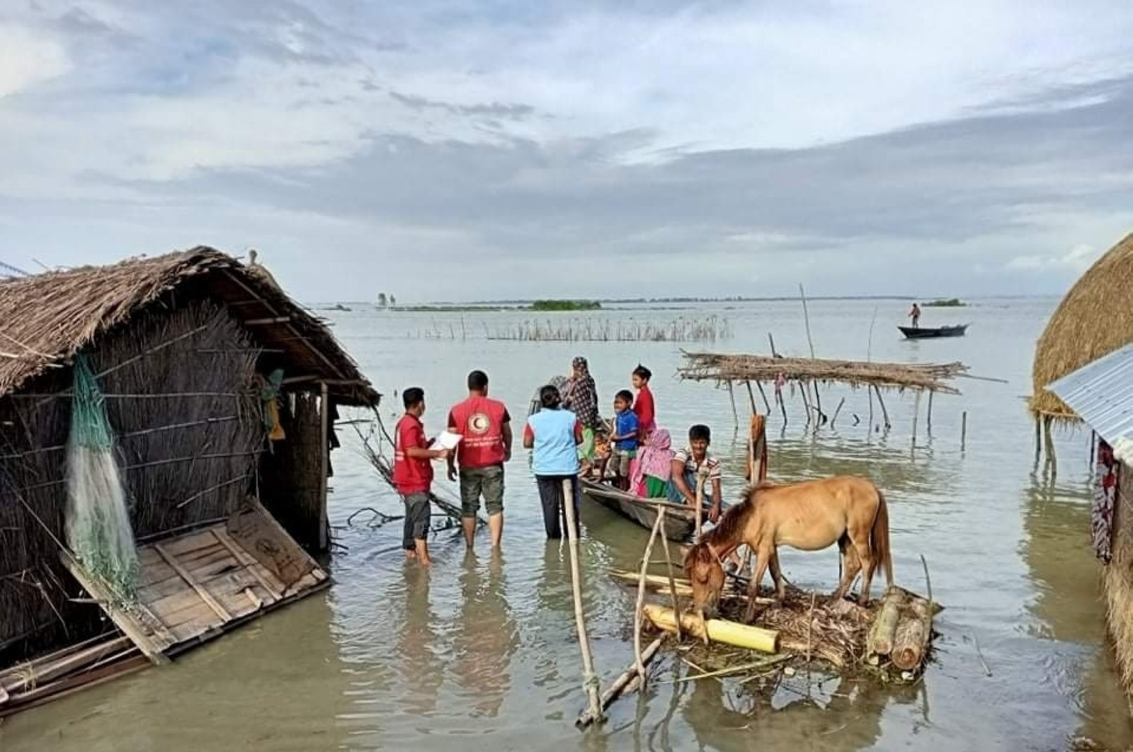 This photograph, provided by the International Federation of Red Cross and Red Crescent Societies (IFRC), shows IFRC volunteers reaching flood-affected communities with drinking water and other support in Kurigram, Bangladesh, July 16, 2020. (AP Photo)
