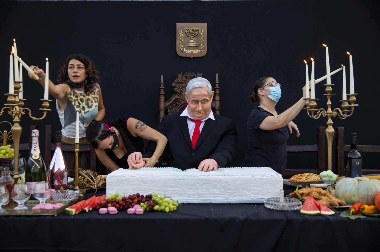 "Team members of Israeli artist Itay Zalait, work on an installation depicting Prime Minister Benjamin Netanyahu at a mock ""Last Supper"" at Rabin square in Tel Aviv, Israel, Wednesday, July 29, 2020. (AP Photo)"