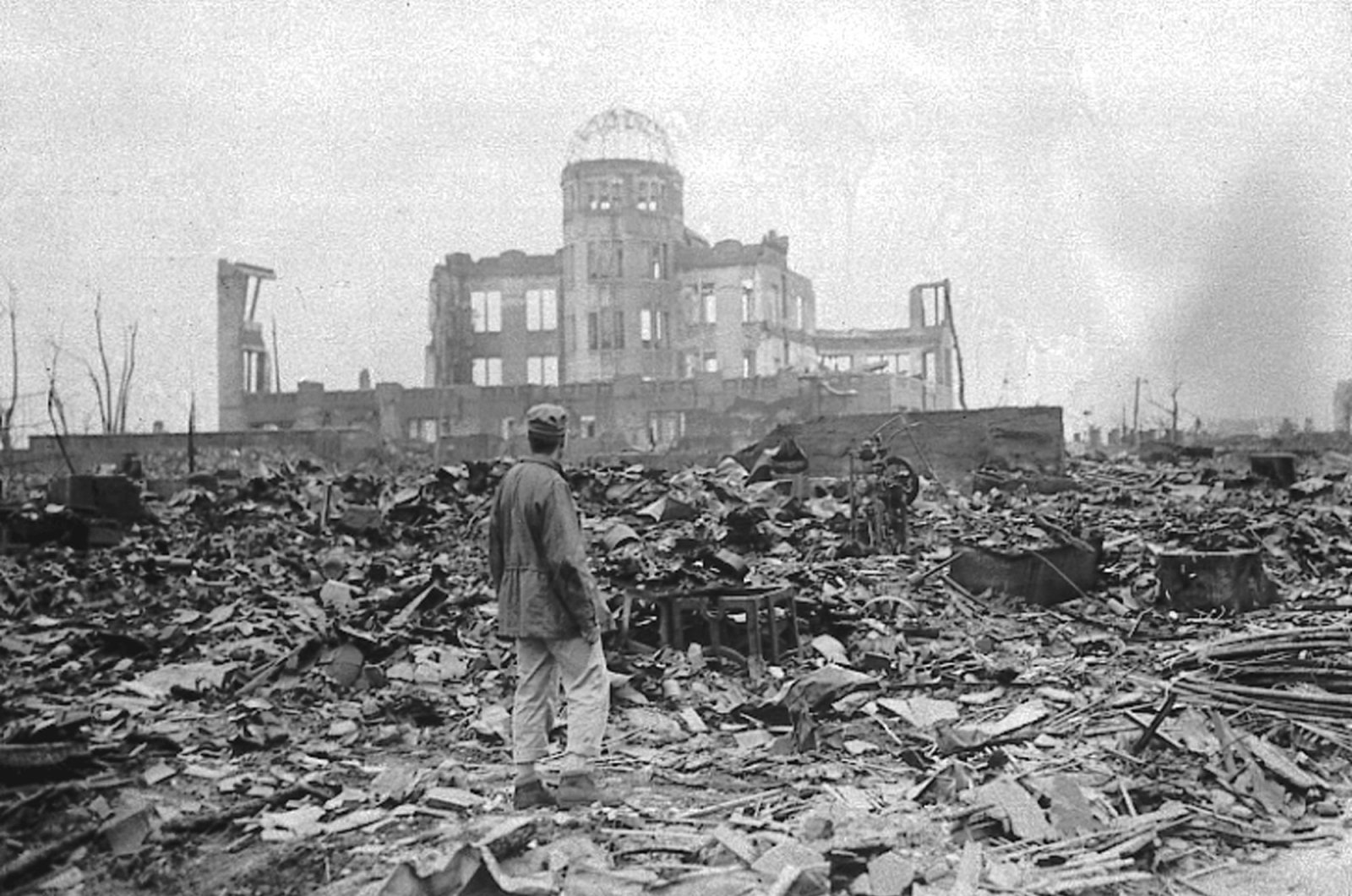 A correspondent stands in a sea of rubble before the shell of a building that once was a movie theater in Hiroshima, Japan, Sept. 8, 1945. (AP Photo)