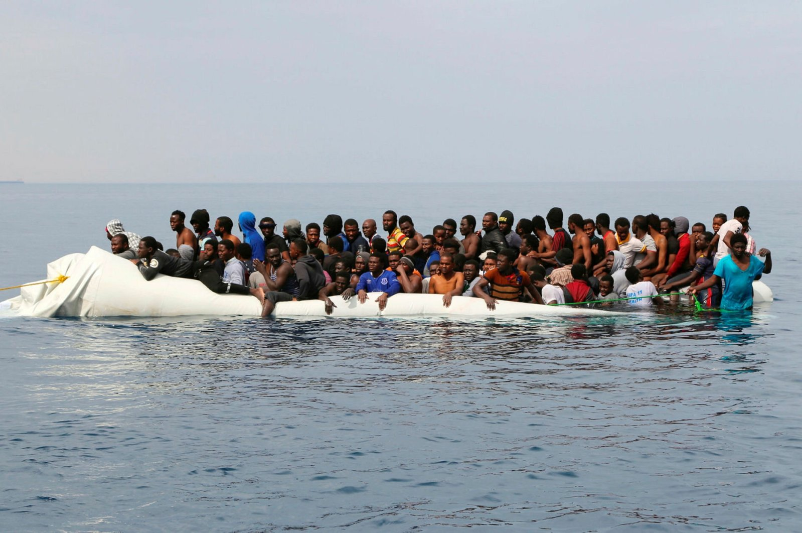 Migrants wait to be rescued from a sinking dinghy off the Libyan coastal town of Zawiyah, east of the capital, after they attempted to cross from the Mediterranean to Europe on March 20, 2017. (AFP Photo)