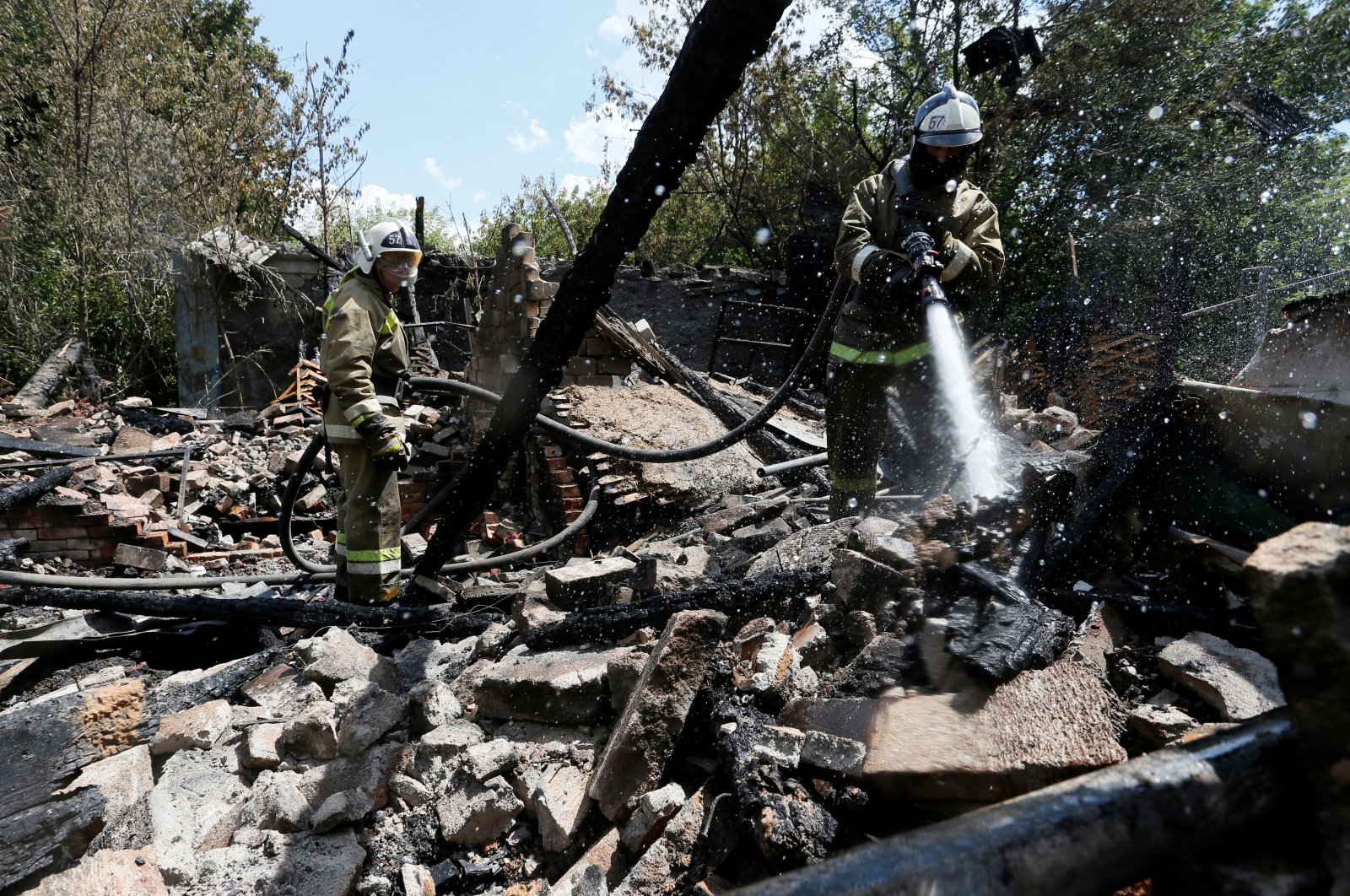 Firefighters work at the ruins of a house in the separatist-controlled city of Donetsk, Ukraine, July 22, 2020. (Reuters Photo)