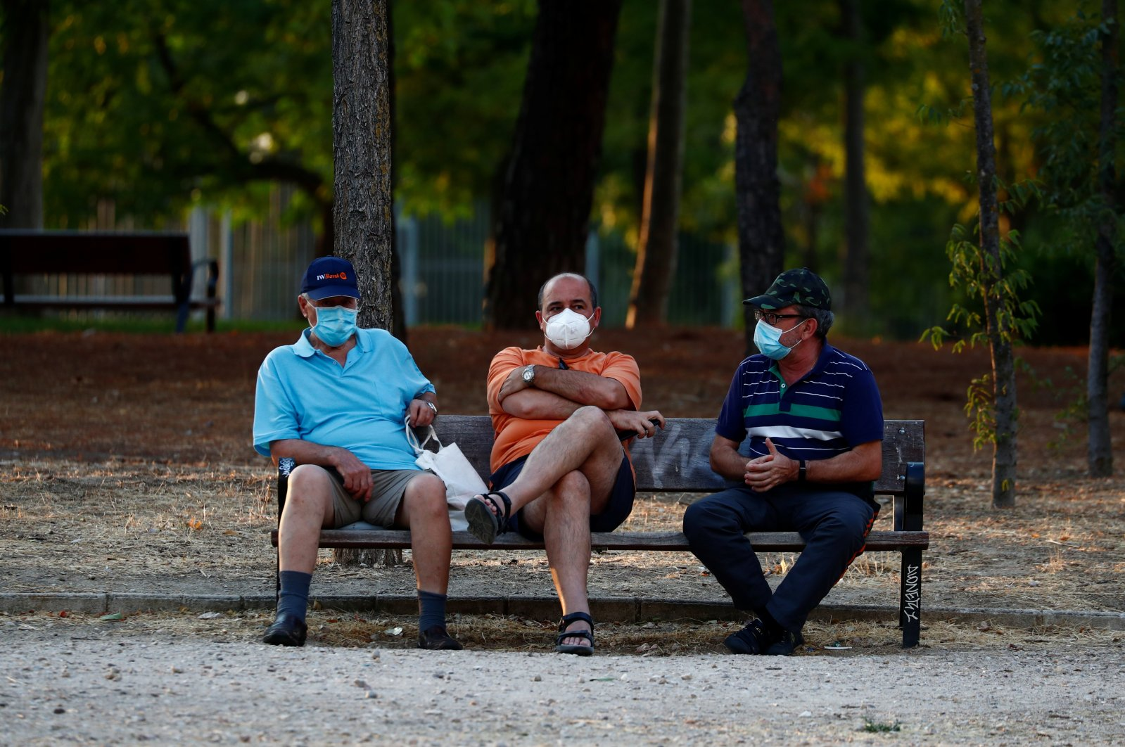 People wearing protective face masks sit at the Las Cruces park amid the coronavirus outbreak in Madrid, Spain, July 28, 2020. (Reuters Photo)